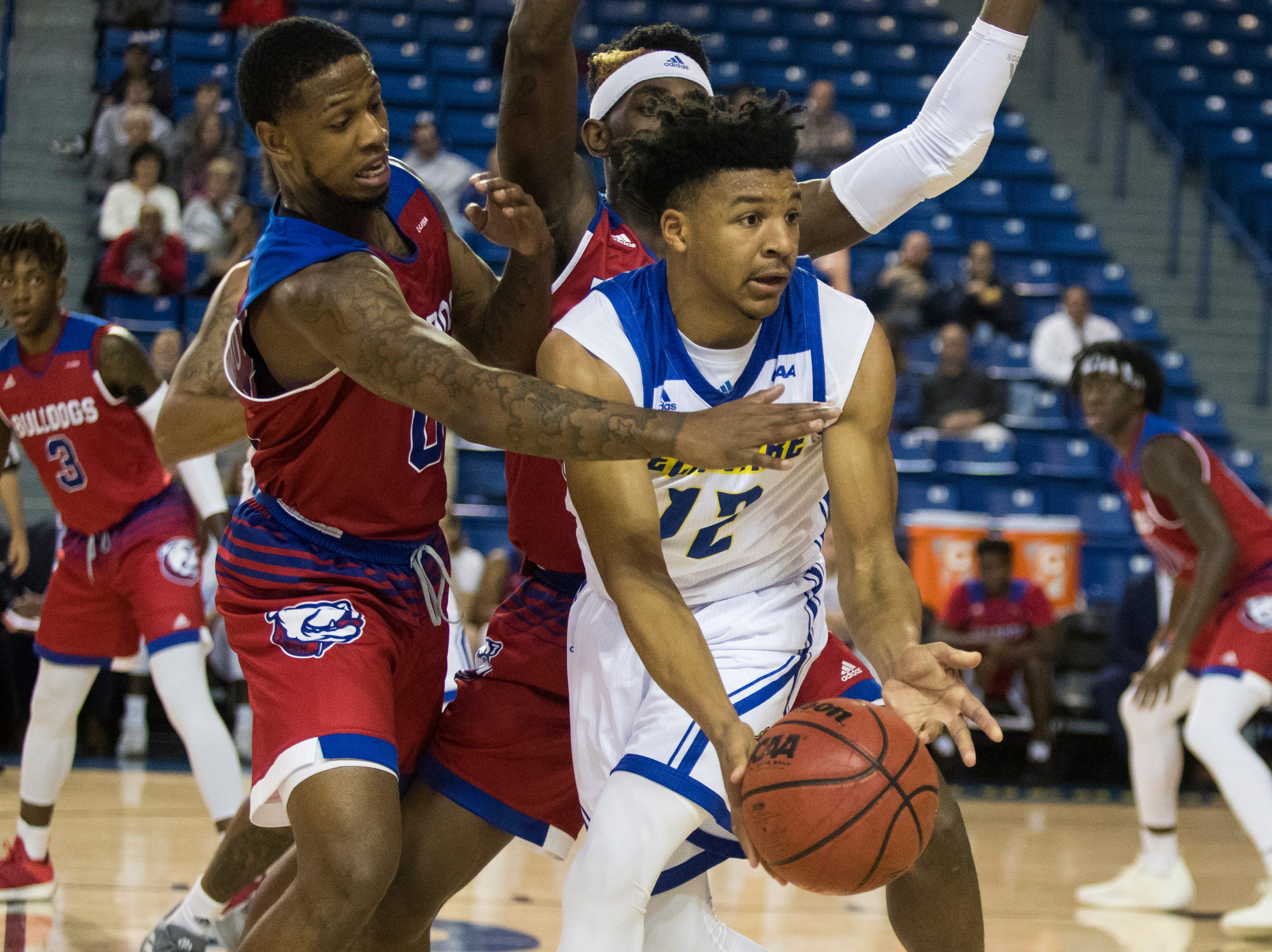 Delaware's Ithiel Horton (12) looks for a teammate to pass too while under pressure from the Louisiana Tech defense Monday at the Bob Carpenter Center. Delaware defeated Louisiana Tech 75-71.