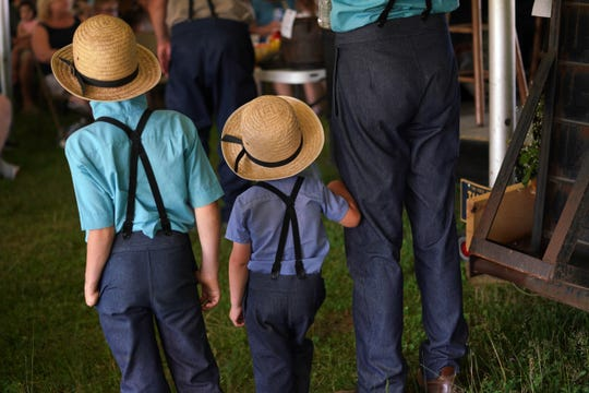 Young Amish boys stand next to their father at an Amish auction.