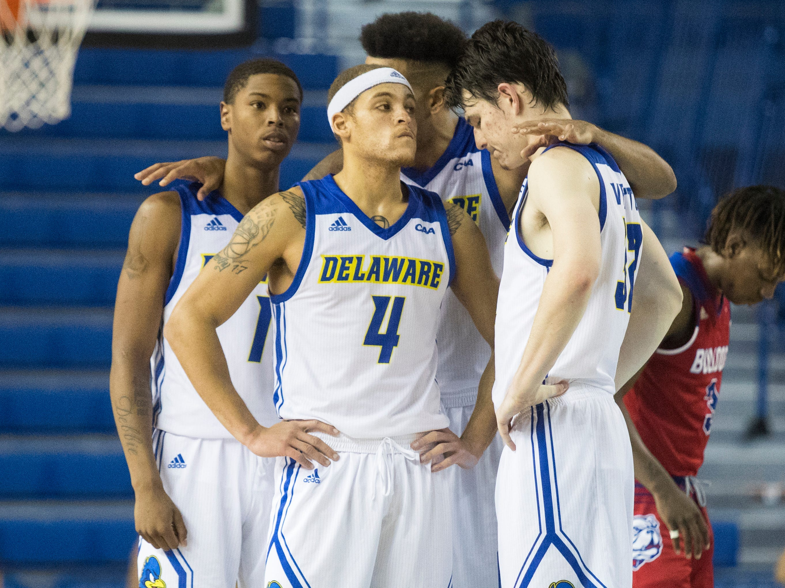 Delaware's Eric Carter (5) speaks with teammates Kevin Anderson (1), Darian Bryant (4), and Matt Veretto (32) Monday at the Bob Carpenter Center. Delaware defeated Louisiana Tech 75-71.