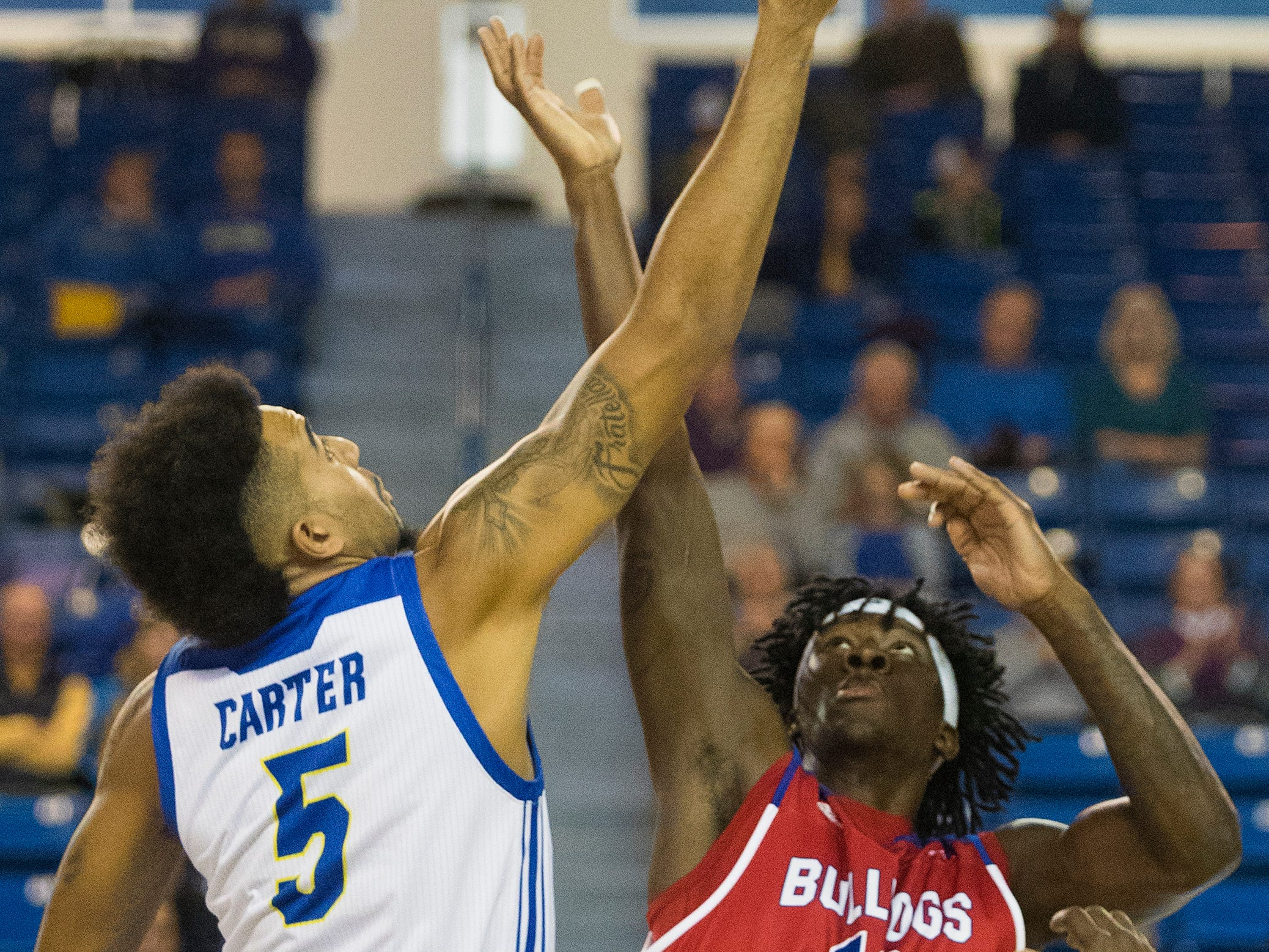 Delaware's Eric Carter (5) reaches the tipoff first against Louisiana Tech's Anthony Duriji (10) Monday at the Bob Carpenter Center. Delaware defeated Louisiana Tech 75-71.