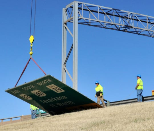 Road crews work to replace large signs along US 287 near Jacksboro Highway Tuesday afternoon.