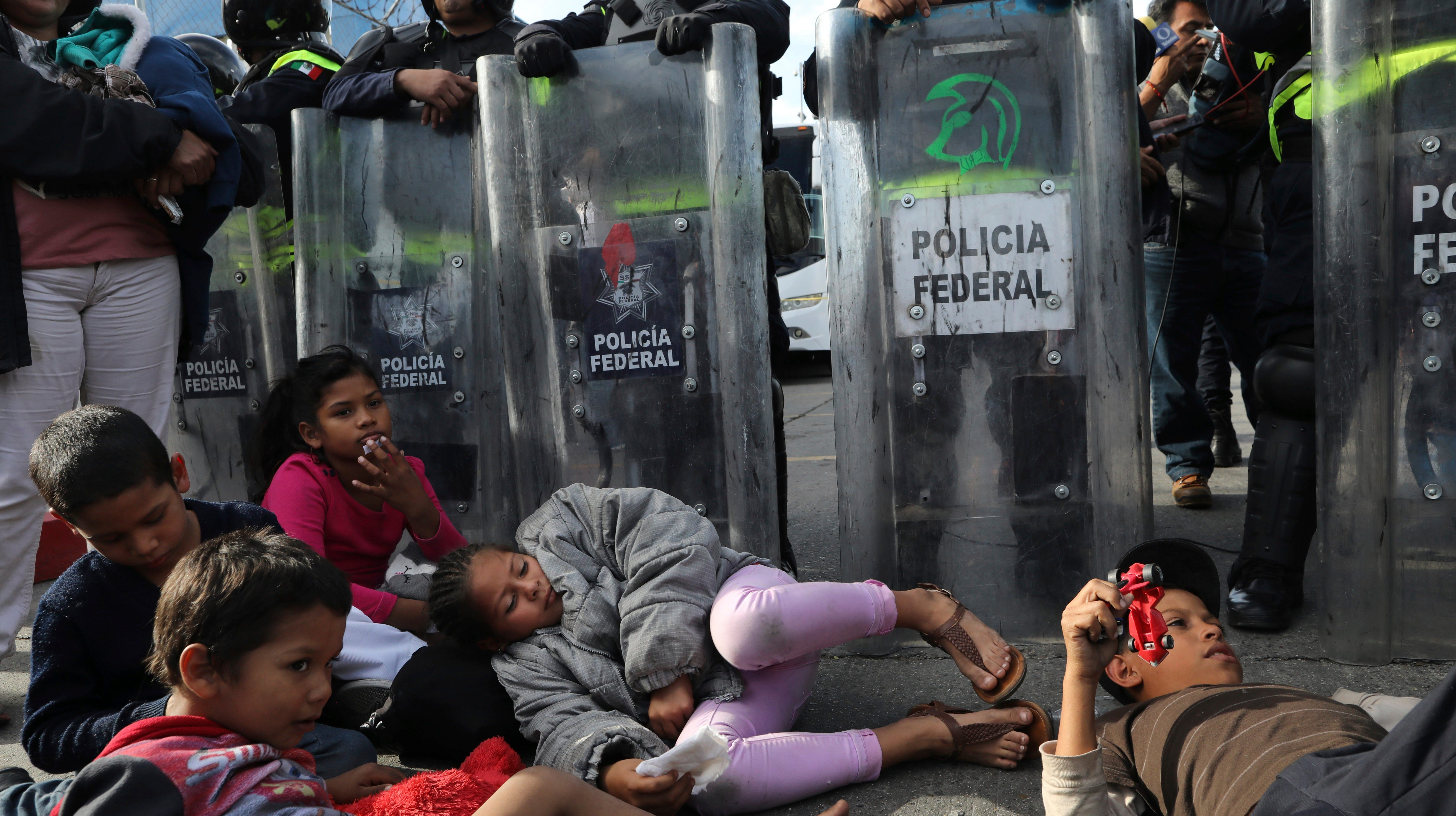 Migrant children rest in front of Mexican police in riot gear in Tijuana on Nov. 22, 2018.