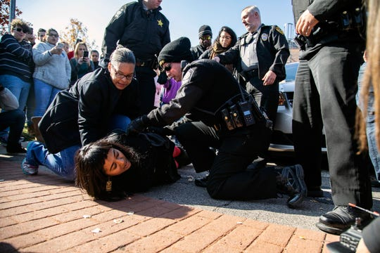 A demonstrator is arrested after Samuel Oliver-Bruno, 47, an undocumented Mexican national, was arrested after arriving at an appointment with immigration officials, in Morrisville, N.C., Friday, Nov. 23, 2018. He had been living in CityWell United Methodist Church in Durham since late 2017 to avoid the reach of immigration officers, who generally avoid making arrests at churches. (Travis Long/The News & Observer via AP) ORG XMIT: NCRAL502