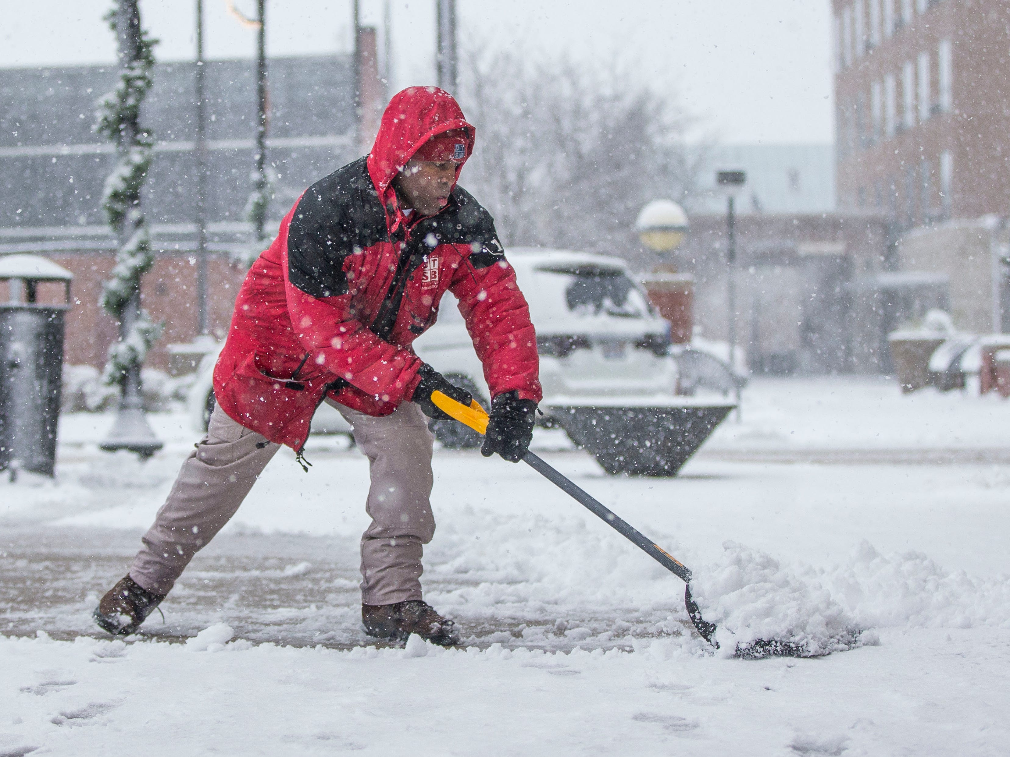 Terrance Pates clears a sidewalk along Michigan Avenue on  Nov. 26, 2018, in South Bend, Ind.