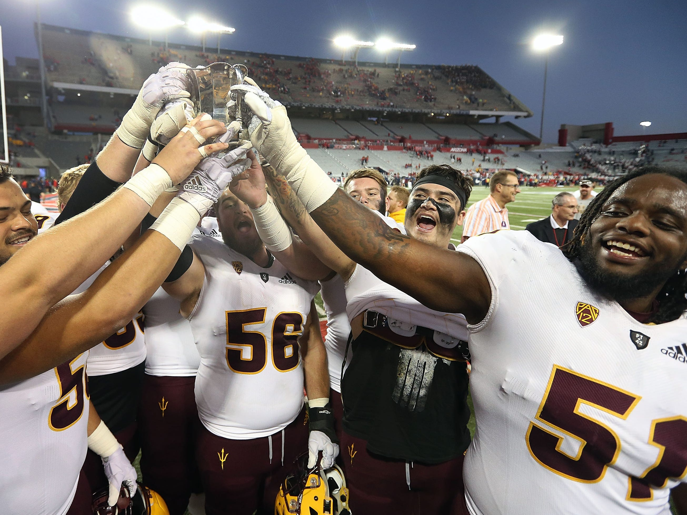 Territorial Cup:  Arizona State players  hold up the Territorial Cup after a 41-40 win over Arizona at Arizona Stadium in Tucson on Nov. 24.