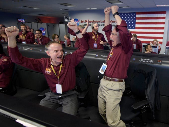 Mars InSight team members Kris Bruvold, left, and Sandy Krasner celebrate on Nov. 26, 2018, inside the Mission Support Area at NASA's Jet Propulsion Laboratory in Pasadena, Calif., after receiving confirmation that the Mars InSight lander successfully touched down on the surface of Mars.