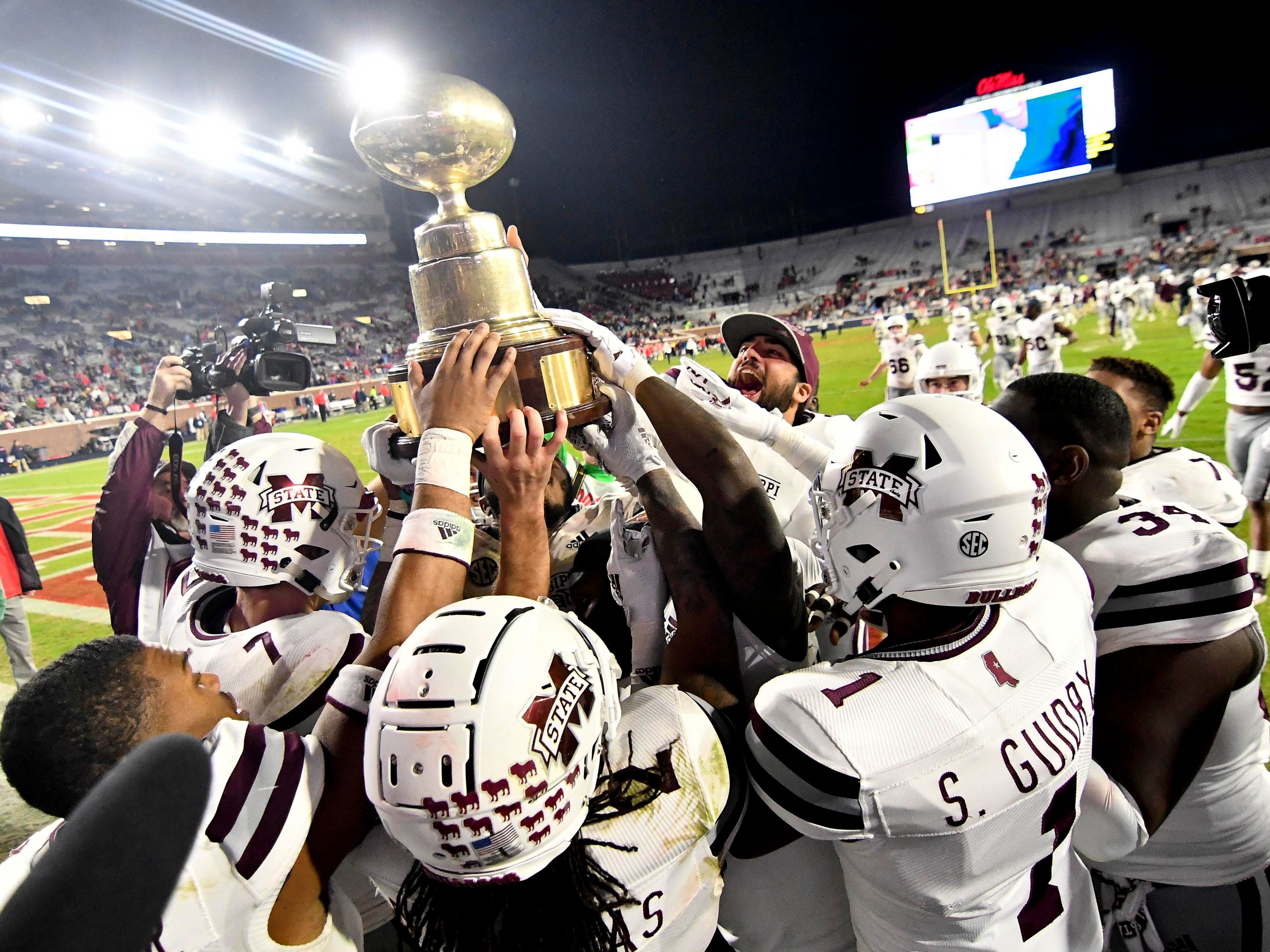 Egg Bowl: Mississippi State players celebrate with the Egg Bowl trophy after defeating Ole Miss, 35-3, at Vaught-Hemingway Stadium on Nov. 22.
