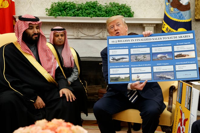 President Donald Trump shows a chart highlighting arms sales to Saudi Arabia during a meeting March 20, 2018, with Saudi Crown Prince Mohammed bin Salman, far left,  at the White House.