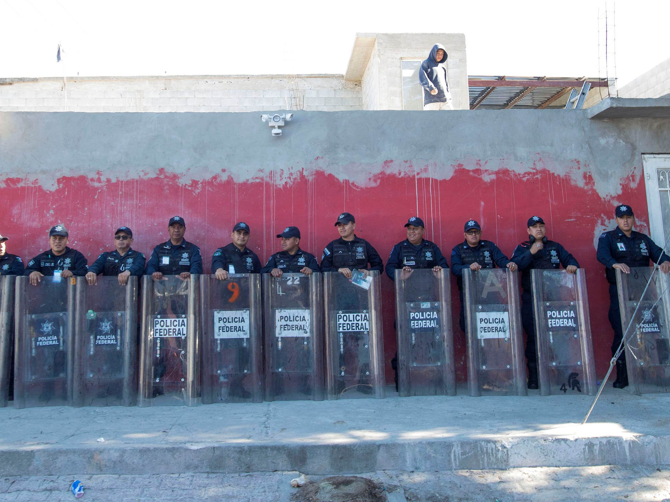 Mexican Federal Police await two blocks away from the Benito Juarez sports complex shelter, Nov. 27, 2018, in Tijuana, Mexico.