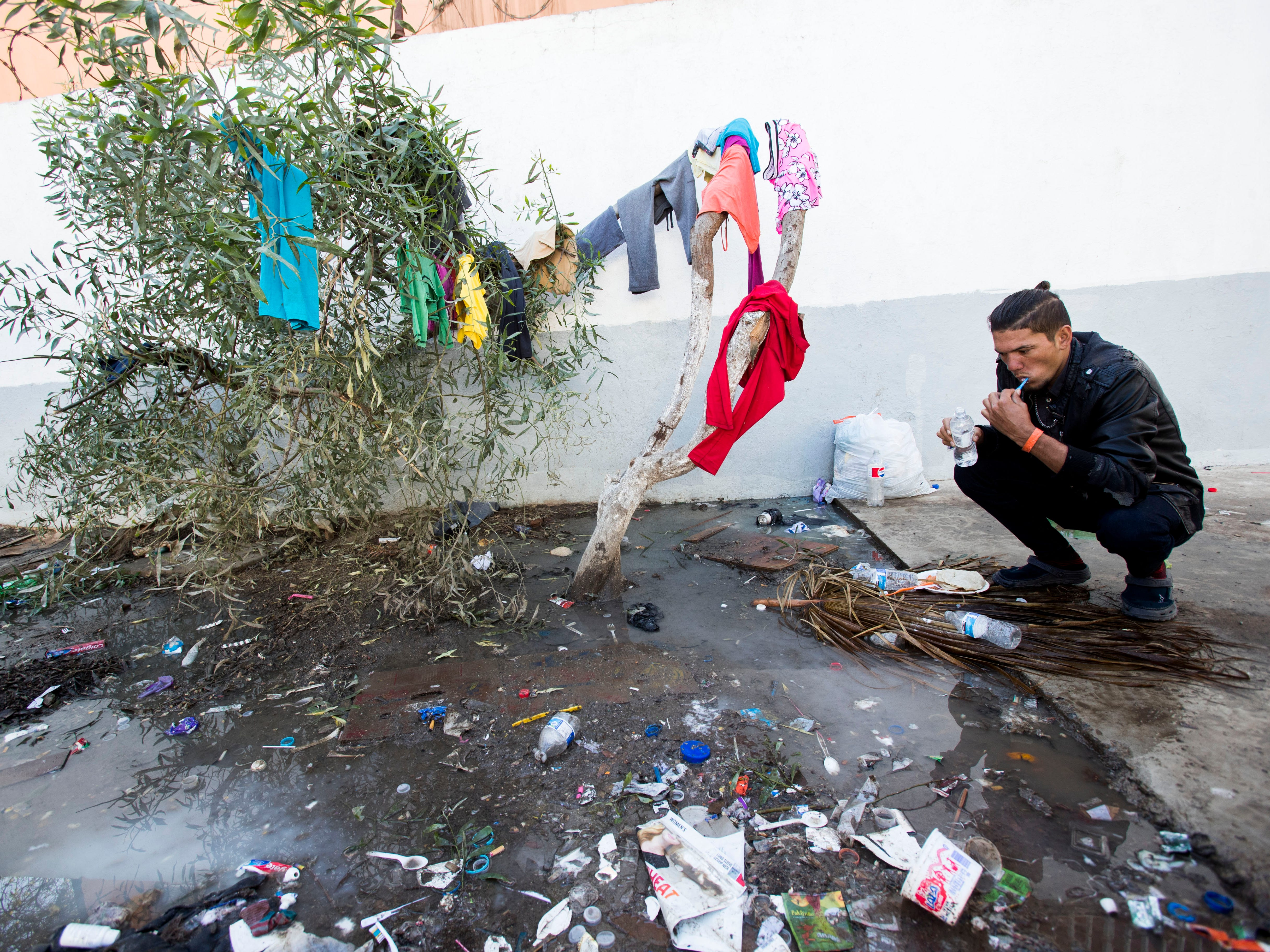 A migrant washes his teeth at the Benito Juarez sports complex shelter, Nov. 27, 2018, in Tijuana, Mexico. The shelter has a maximum capacity of housing 3000 and is currently housing 5851 migrants inside the sports complex turned shelter.