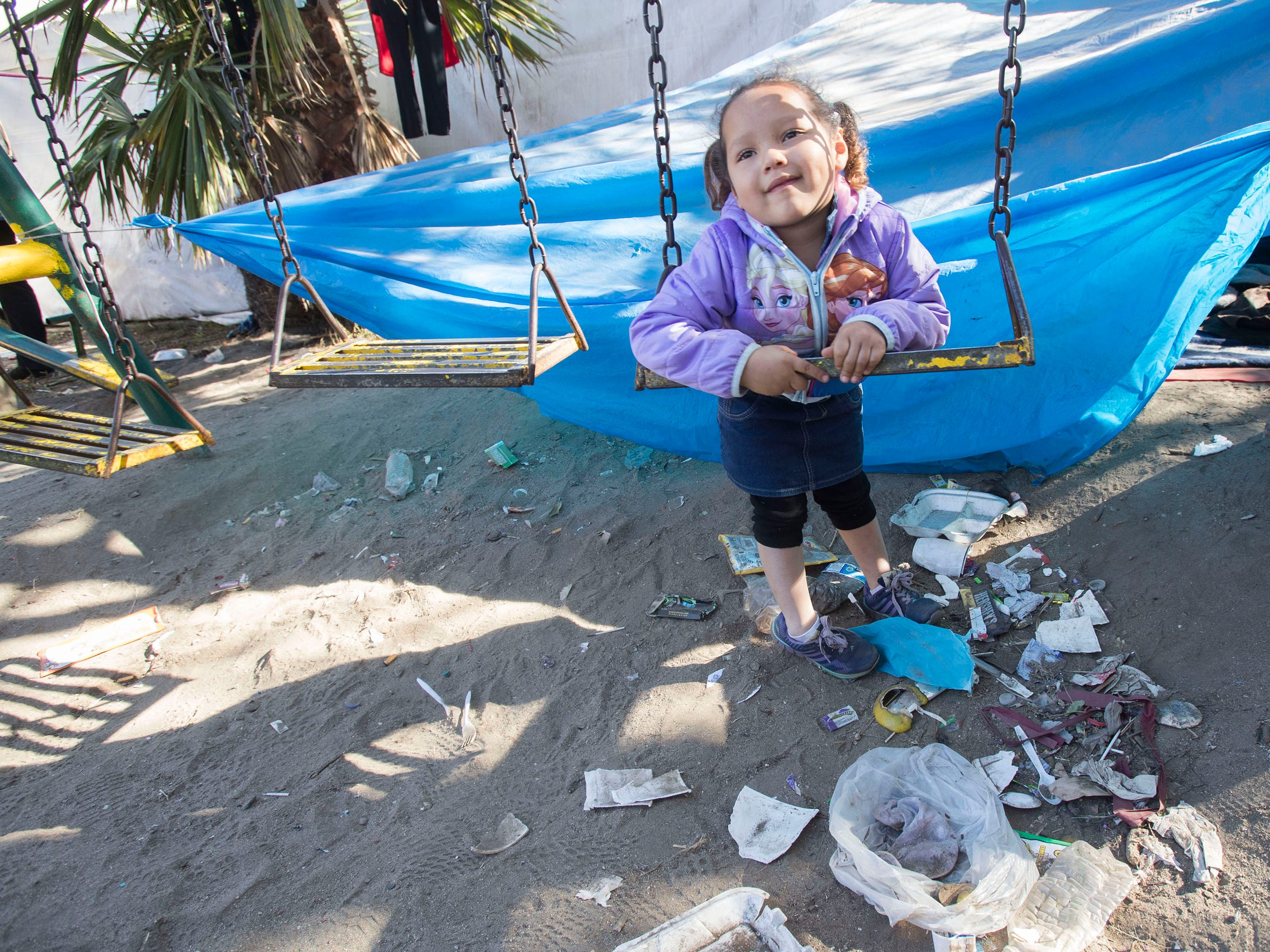 Marbella Figueroa, a three-year-old, plays on a swing as thrash sits at her feet at the Benito Juarez sports complex shelter, Nov. 27, 2018, in Tijuana, Mexico.