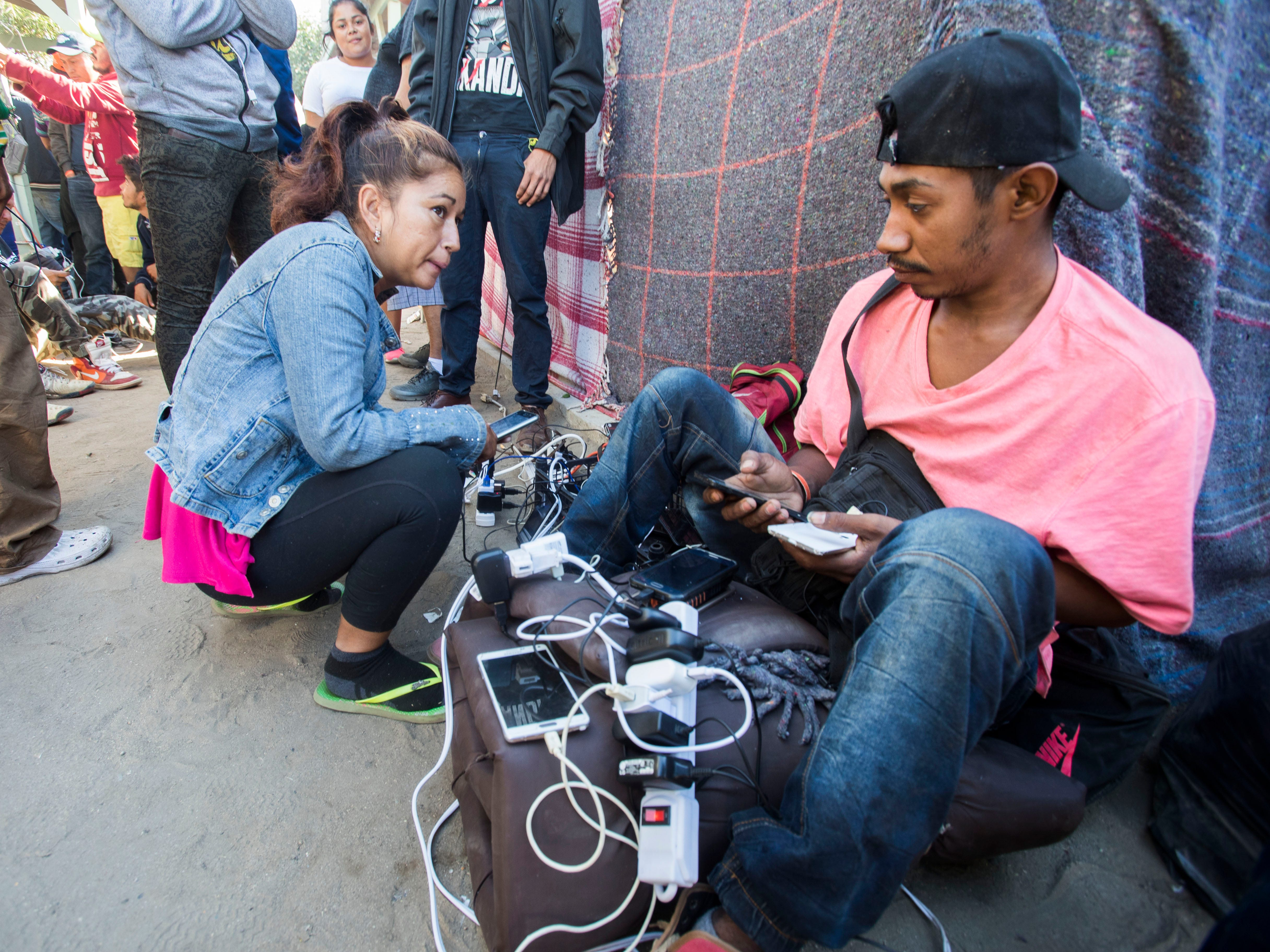 Migrants charge their phone batteries at the Benito Juarez sports complex shelter, which is housing more than 5000 migrants in the city of Tijuana, Mexico on Nov. 27, 2018.