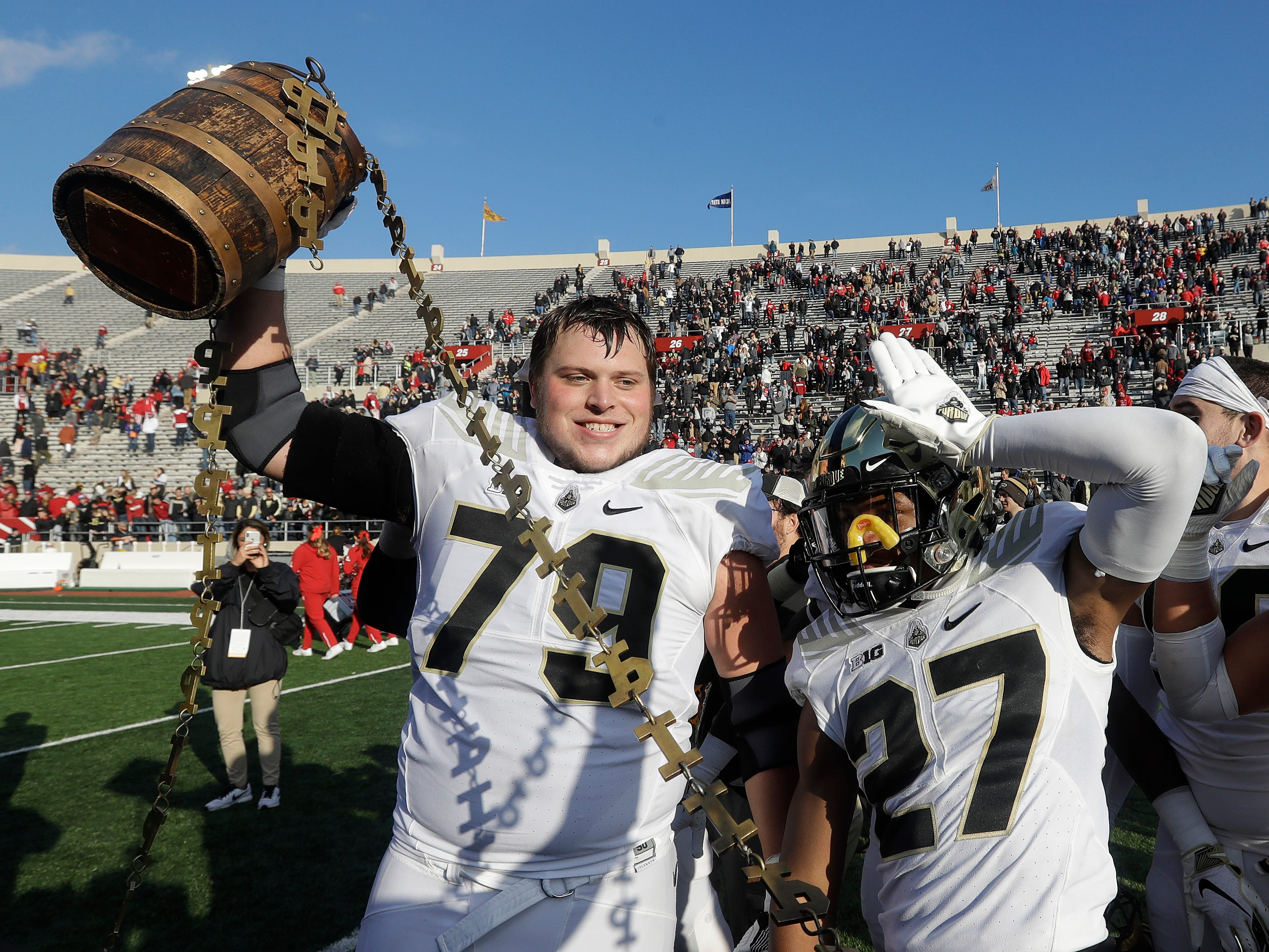 Old Oaken Bucket: Purdue's Matt McCann (79) and Navon Mosley (27) celebrates with the Old Oaken Bucket after defeating Indiana, 28-21, in Bloomington, Ind. on Nov. 24.