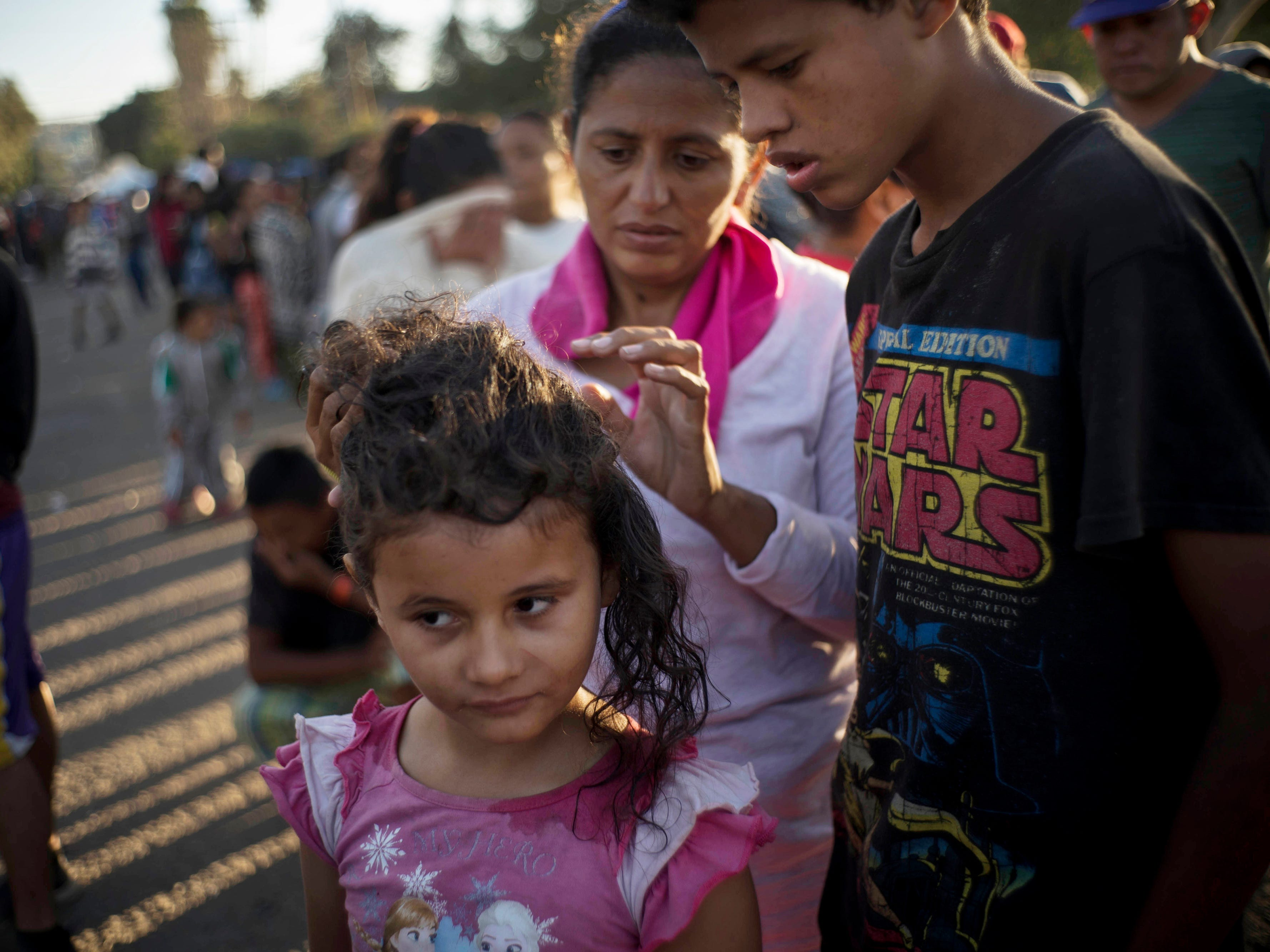 Marlen Castillo looks for head lice on her daughter, Belen, while they stand in line to receive food at the Benito Juarez Sports Center in Tijuana, Mexico on Nov. 26, 2018.