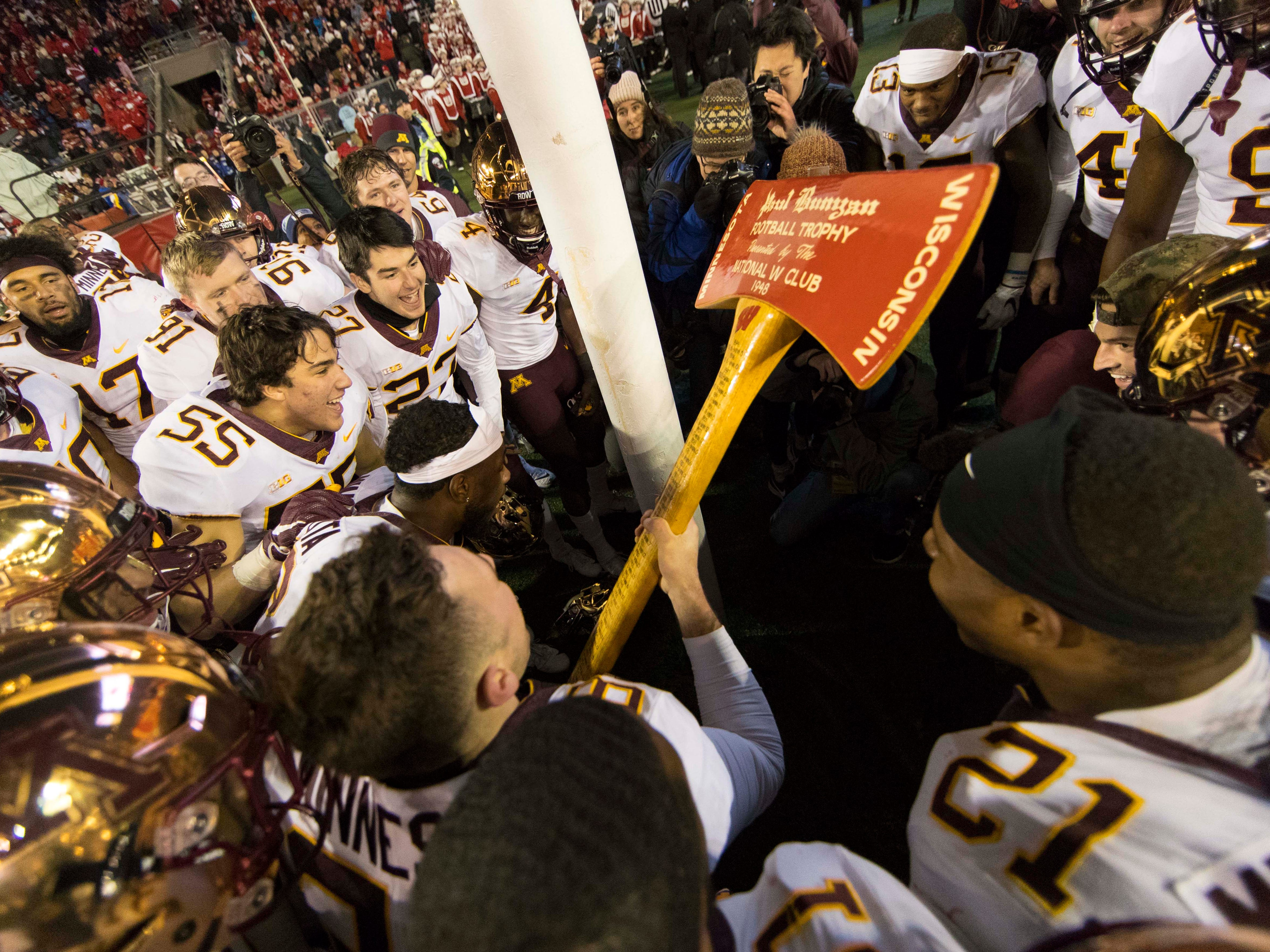Paul Bunyan's Axe: Minnesota players celebrate with the Axe after a 37-15 win over Wisconsin at Camp Randall Stadium on Nov. 24.