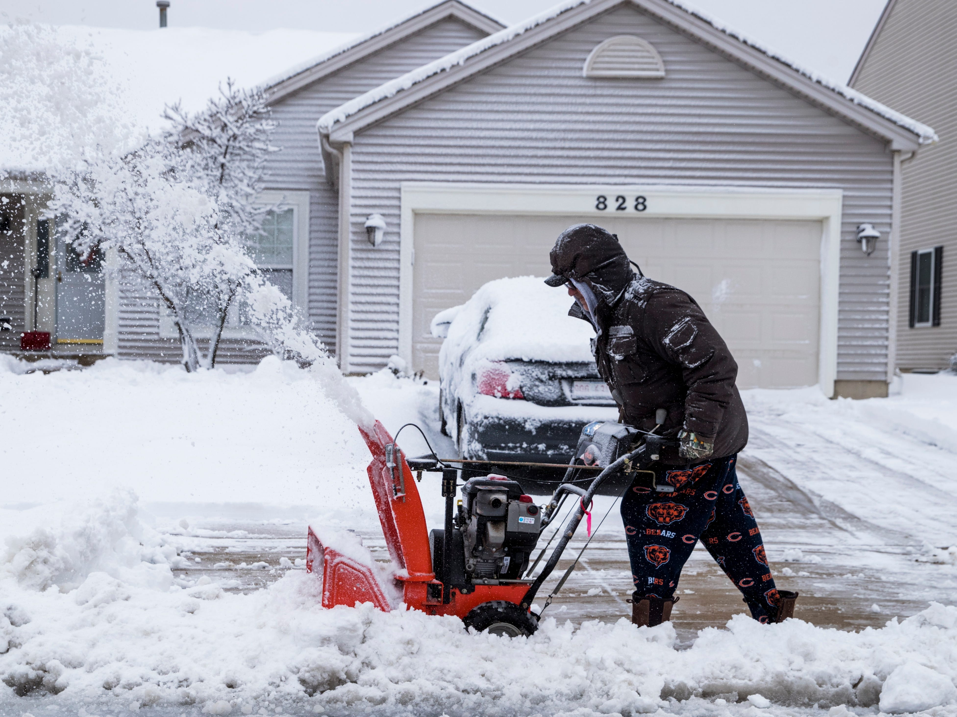 A man uses a snow blower on Nov. 26, 2018, to clear his driveway after a winter storm dumped nearly a foot of snow in Round Lake, Ill.