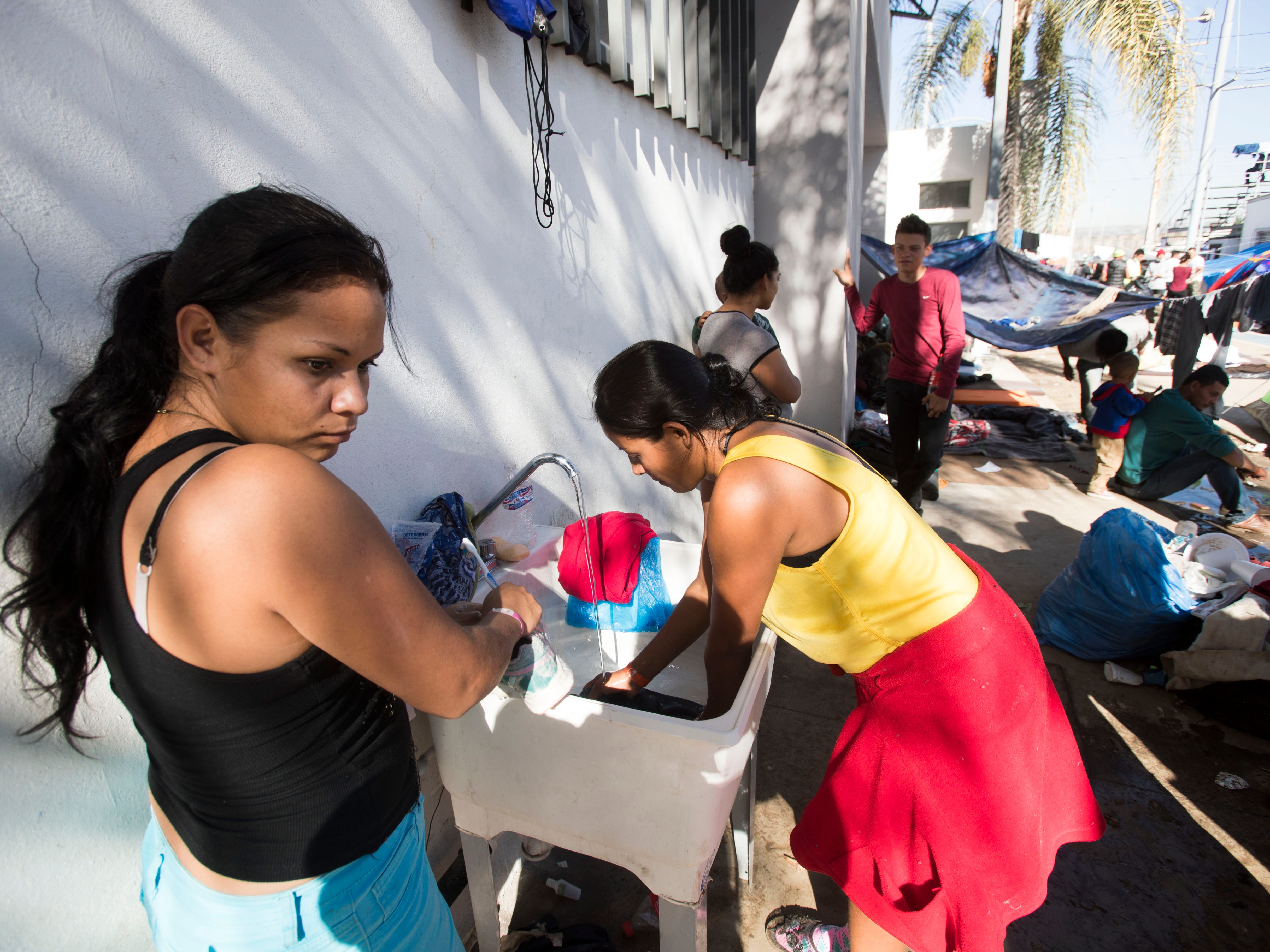 Women and men take turns to wash clothes in one of two sinks at the Benito Juarez sports complex shelter, Nov. 27, 2018, in Tijuana, Mexico.