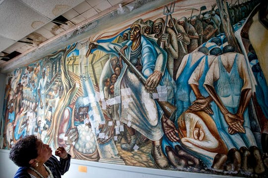 """In a Wednesday, Nov. 7, 2018 photo, Charlotte Bryant looks at the John Biggers mural, """"Contribution of Negro Women to American Life and Education"""" that was damaged in the aftermath of Hurricane Harvey, at the Blue Triangle Community Center, in Houston. The historic mural was temporarily treated to prevent mold from spreading across it, but still needs extensive work to fully restore the work of art and the building in which it is housed.  (Brett Coomer/Houston Chronicle via AP)"""