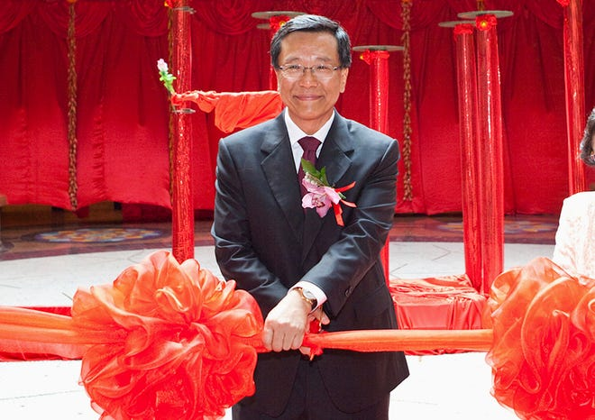 Chairman of the Malaysian Genting Group Tan Sri Lim Kok Thay cuts a ceremonial ribbon to open a  casino in Singapore. The Genting Group is seeking at least $1 billion in damages from Walt Disney Co. and Fox Entertainment Group for alleged breach of contract related to a theme park.