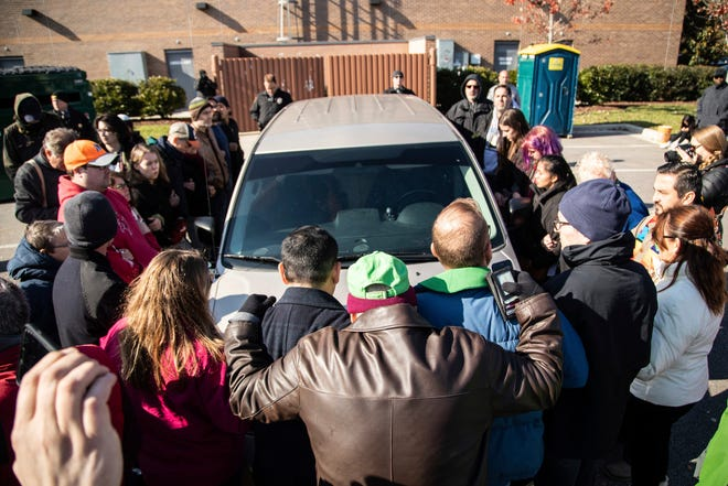 Demonstrators surround a government vehicle after Samuel Oliver-Bruno, 47, an undocumented Mexican national, was arrested after arriving at an appointment with immigration officials, Friday, Nov. 23, 2018, in Morrisville, N.C. He has been living in CityWell United Methodist Church in Durham since late 2017 to avoid the reach of immigration officers, who generally avoid making arrests at churches.  (Travis Long/The News & Observer via AP) ORG XMIT: NCRAL501