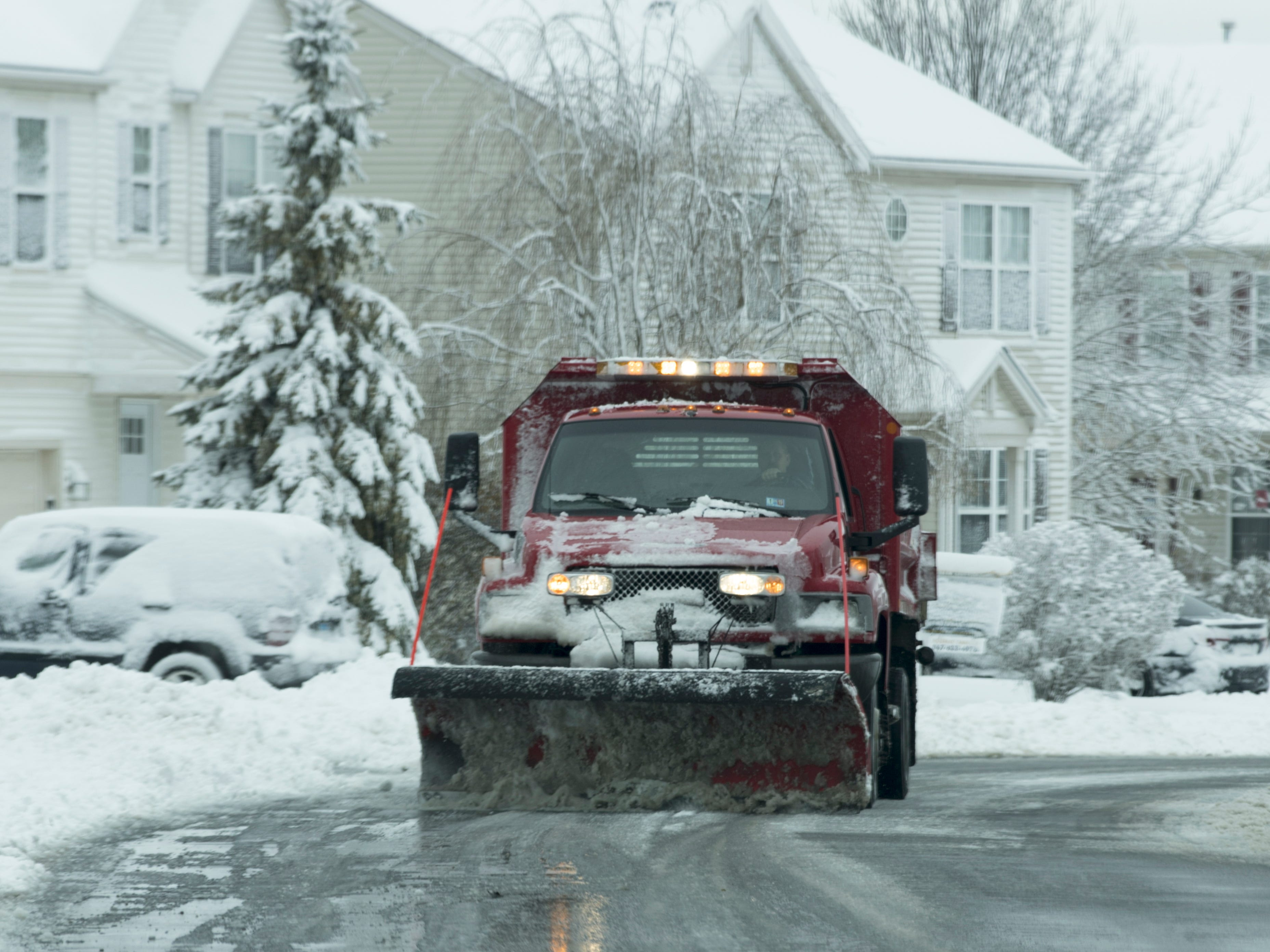 A snow plow clears streets on Nov. 2018, after a winter storm dumped nearly a foot of snow in Round Lake, Ill. The storm left snowy roads, cancelled flights and power outages in its wake as it moves east.