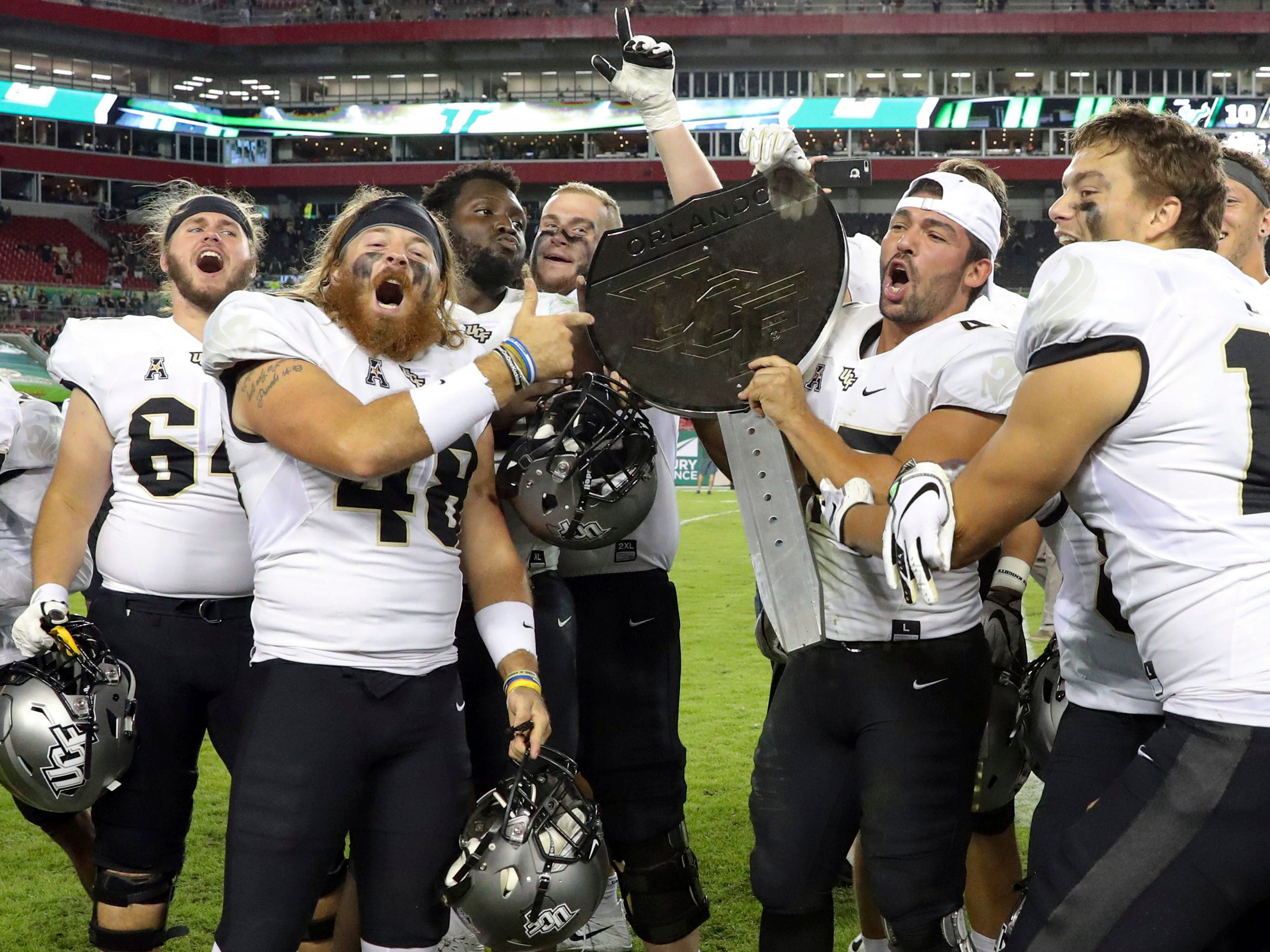 War on I–4 Trophy: Central Florida players celebrate with the War on I-4 trophy after defeating South Florida, 38-10,  in Tampa, Fla. on Nov. 23.