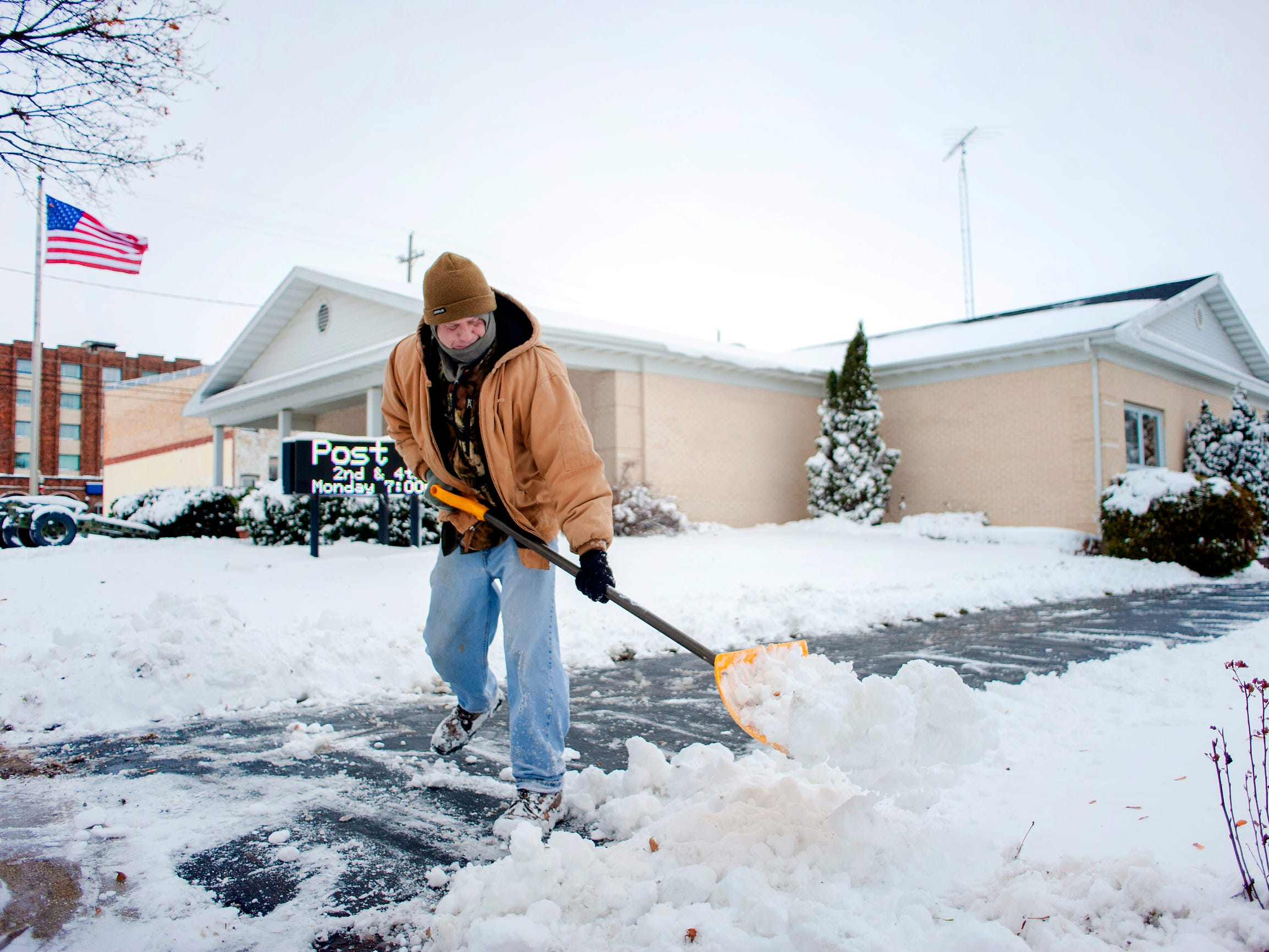 John Loomer, commander of the American Legion Post 95 in Delavan, Wis., shovels walkways around the post building on Nov. 26, 2018. Loomer is a teacher at Lakeland School in Elkhorn, Wis. and had the day off because of the weather conditions.