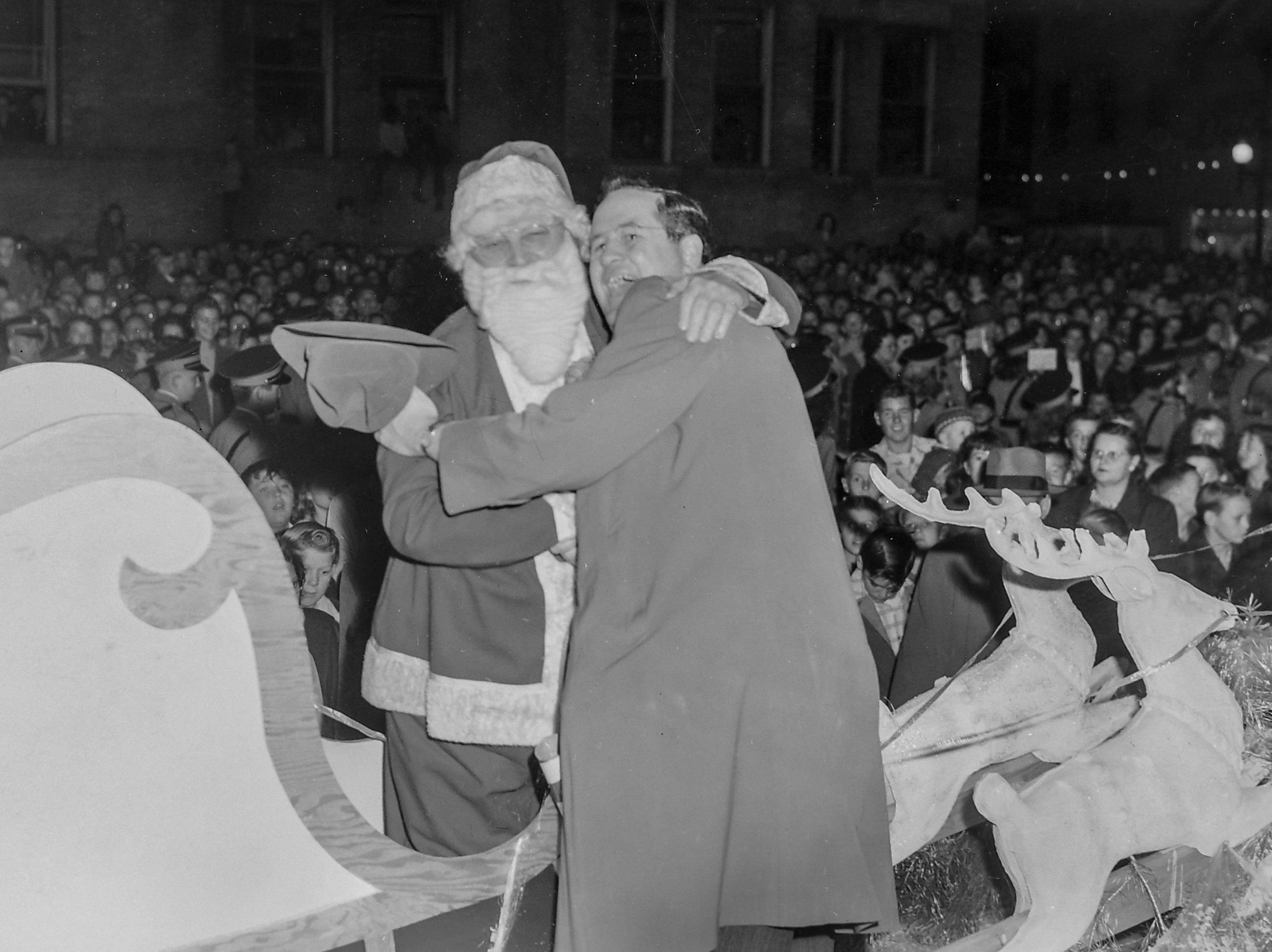 Santa Claus is greeted by a man at the Anderson Christmas Parade on December 1949 in downtown Anderson.