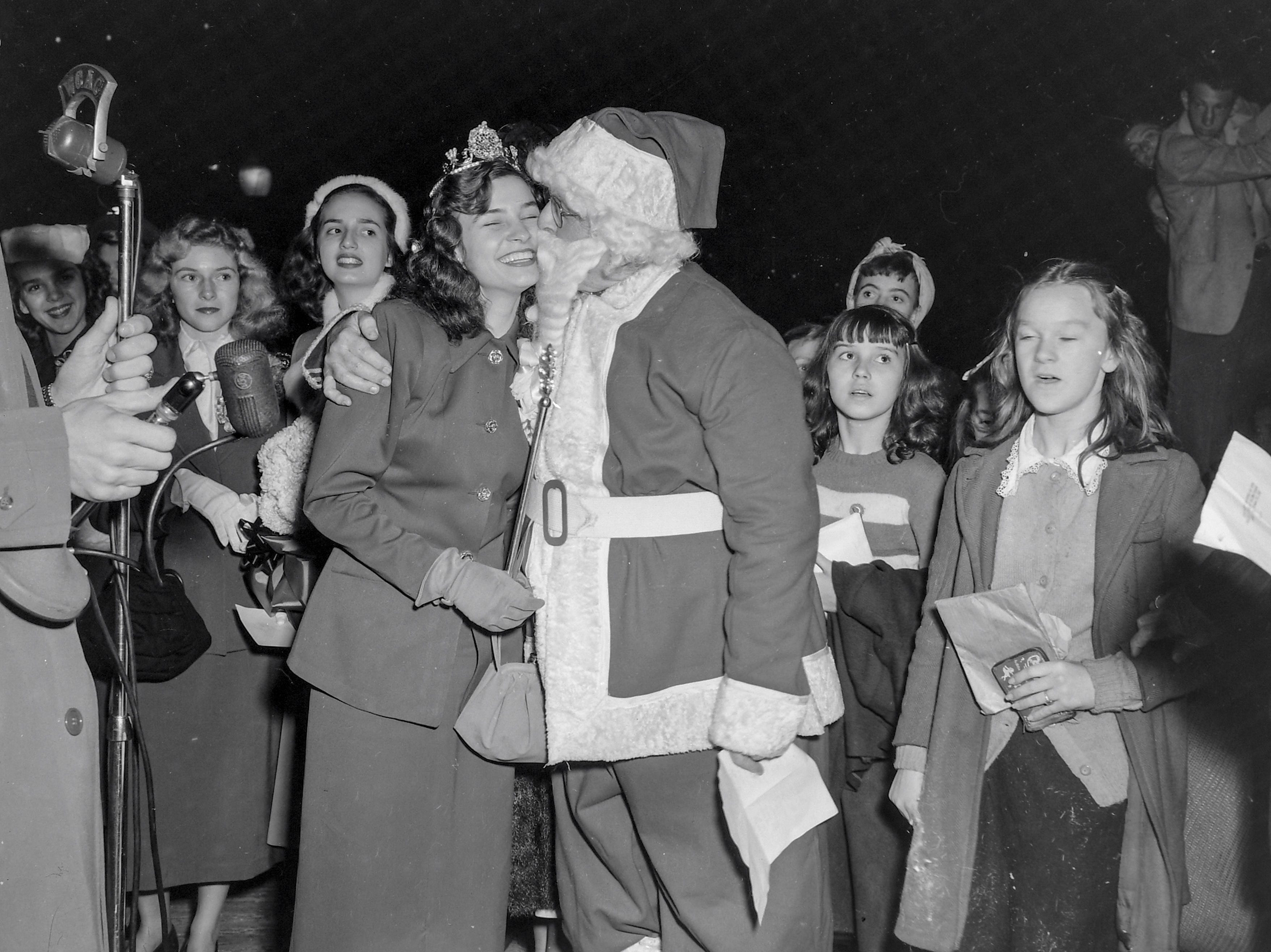 Santa Claus hugs one of the beauty queens participating in the Anderson Christmas Parade on December 1949 in downtown Anderson.