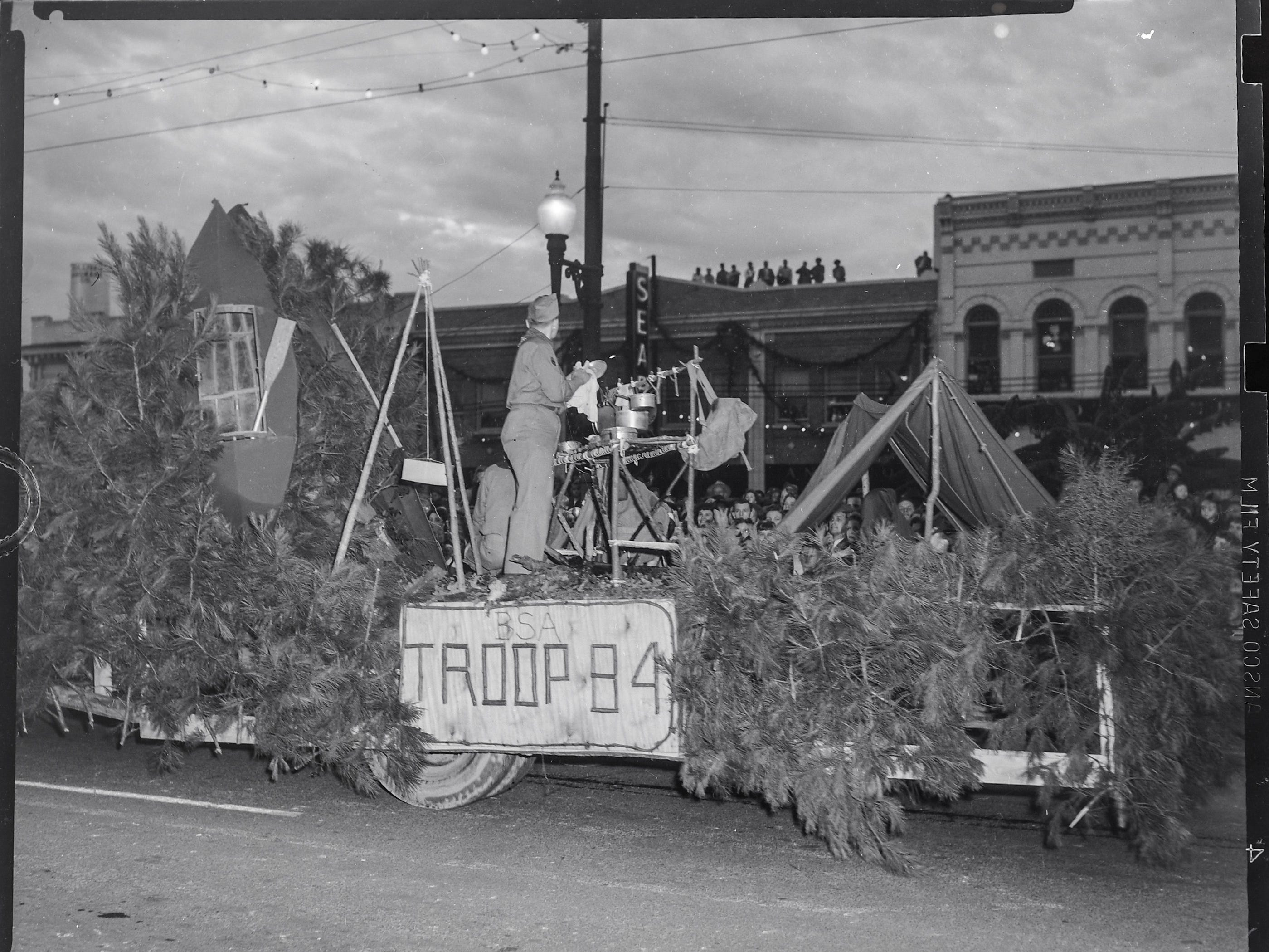 Boy Scouts of America Troop 84 of Central Presbyterian Church in Anderson, on their float decorated like a campsite, pass viewers both on the ground and on the rooftops along Main Street in Anderson, during the Anderson Christmas Parade on December 1949.
