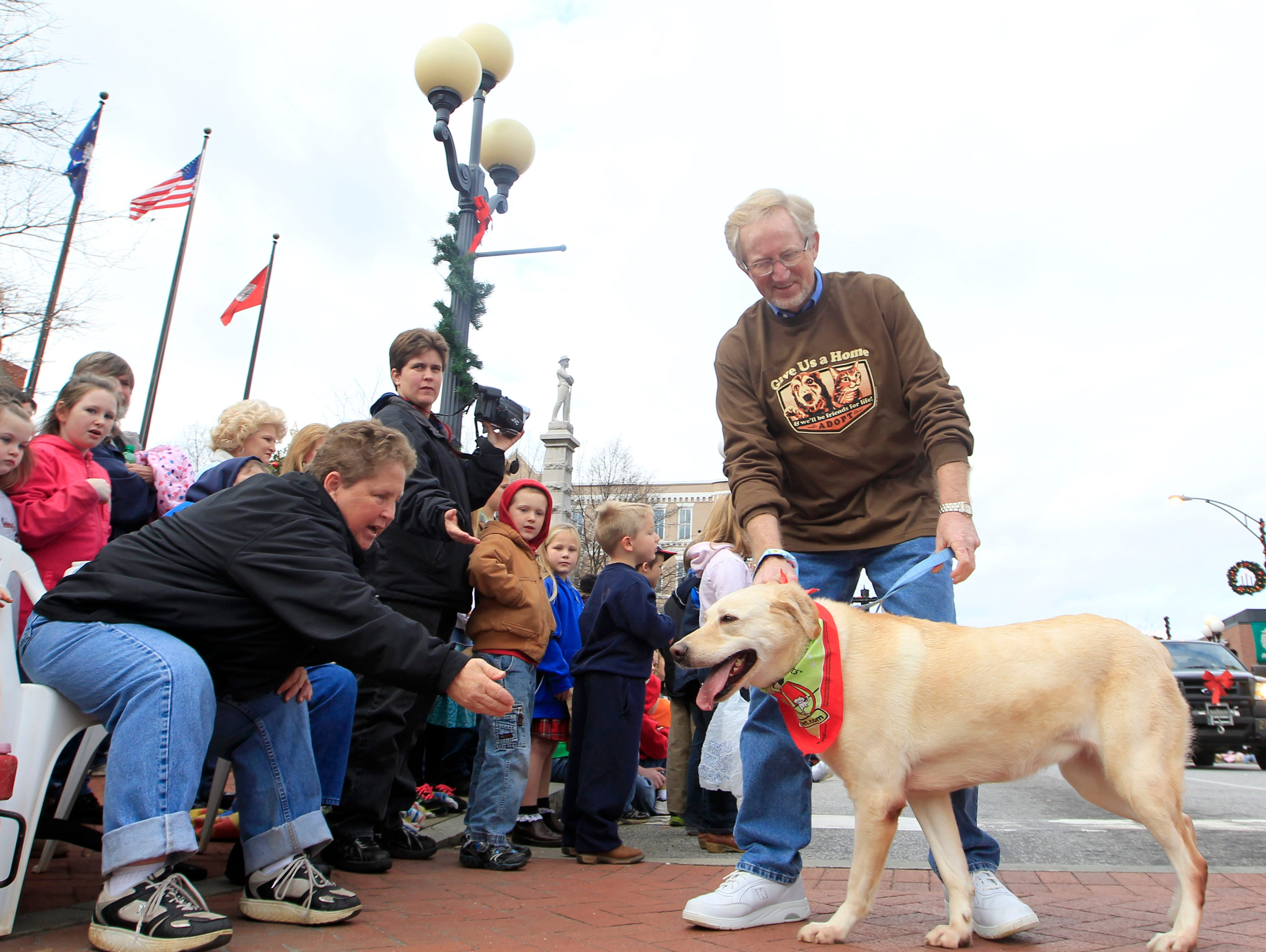 Ray Harrison brings Bailey, a dog from the Anderson County PAWS animal shelter and participant in Sunday's Christmas parade, to spectators on Main Street in 2011.