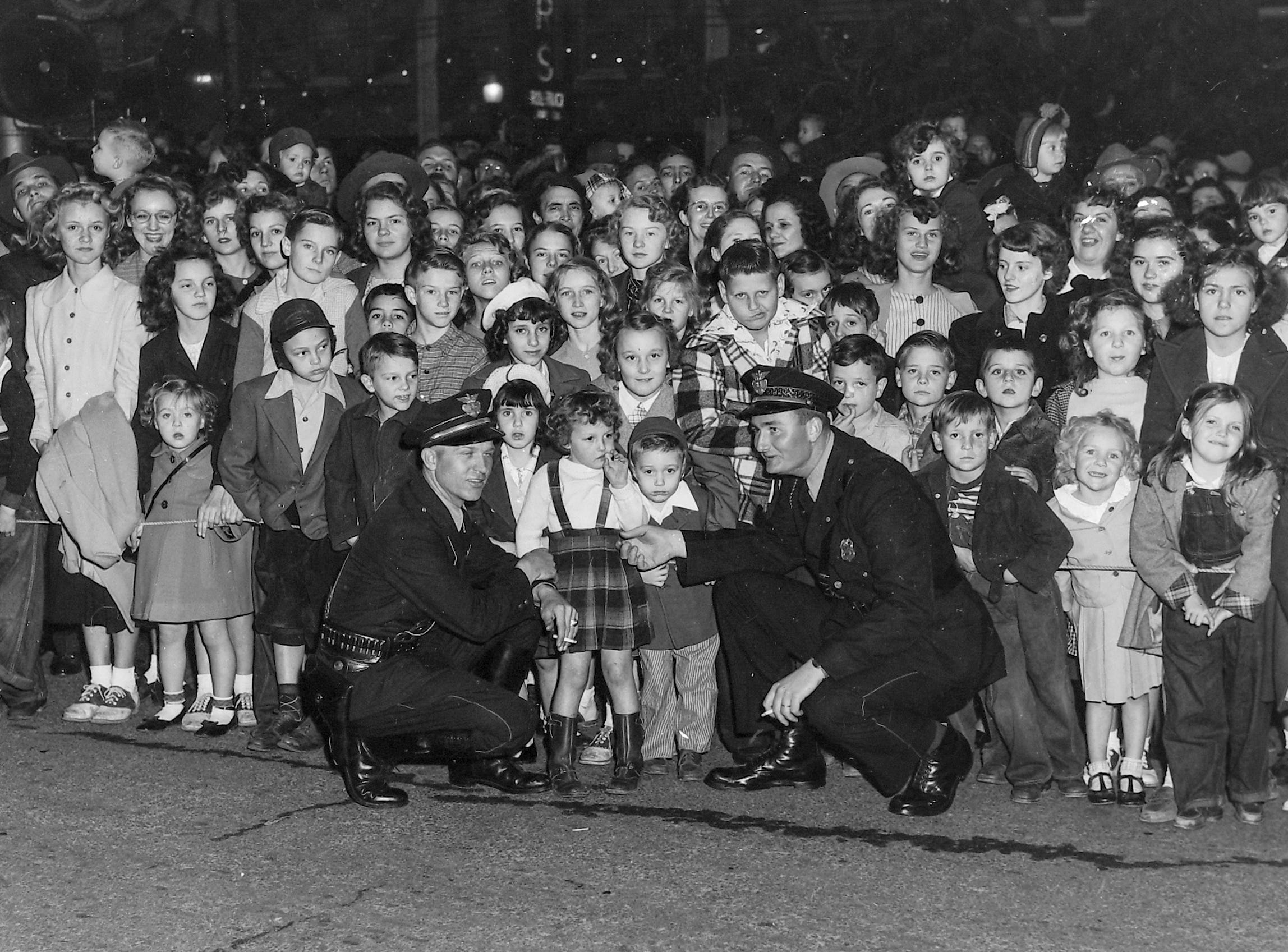 Anderson police kneel next to children at the Anderson Christmas Parade on December 1949 in downtown Anderson.
