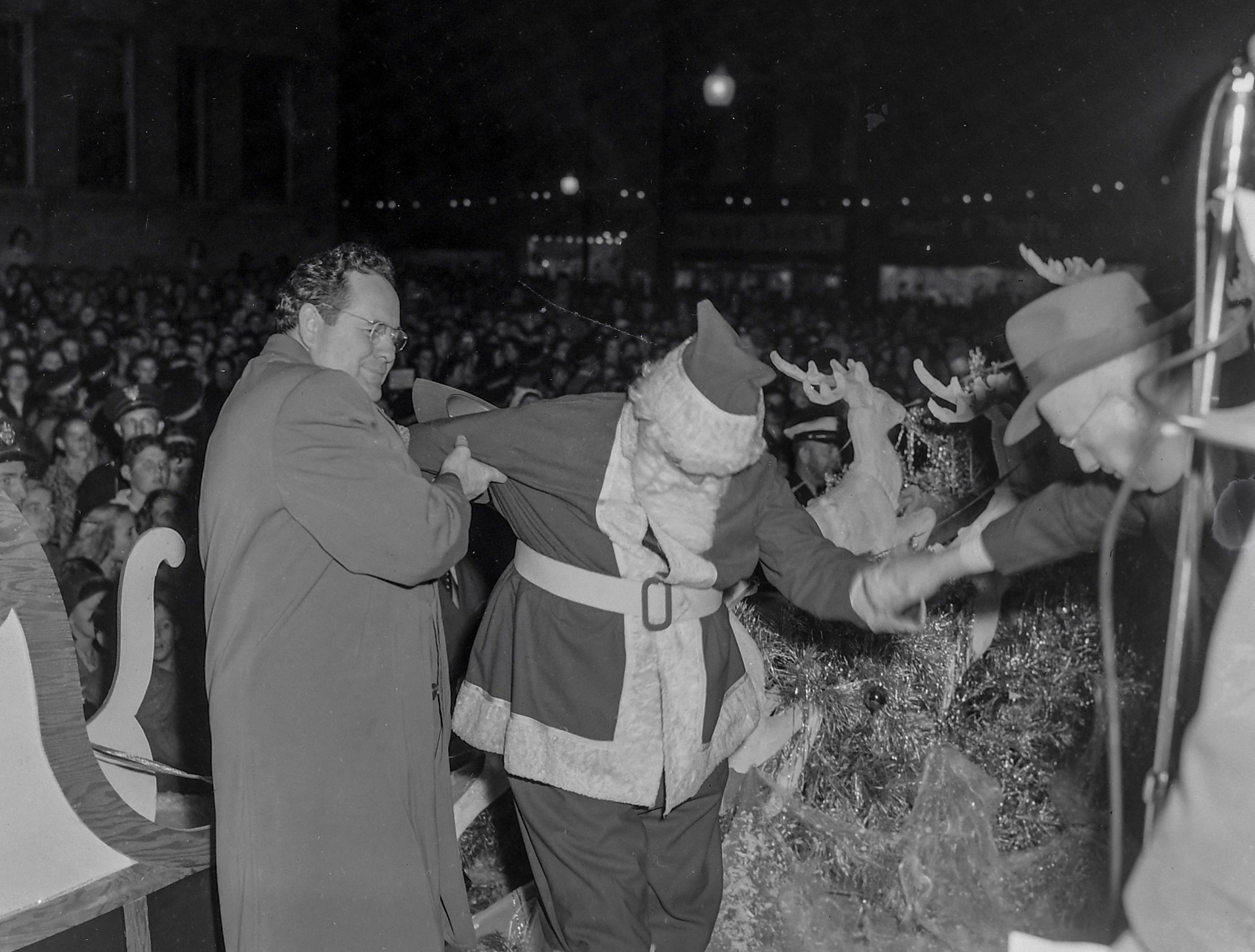 Santa Claus is helped off the sleigh at the Anderson Christmas Parade on December 1949 in downtown Anderson.