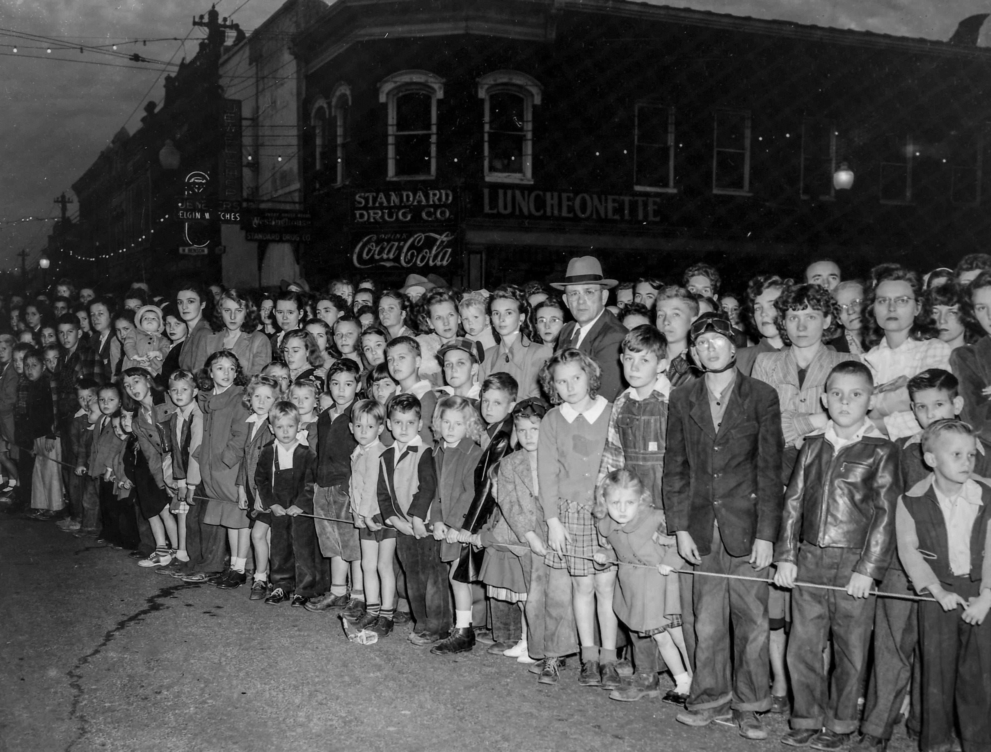 Children and adults stand behind barrier ropes for the Anderson Christmas Parade on December 1949 in downtown Anderson.