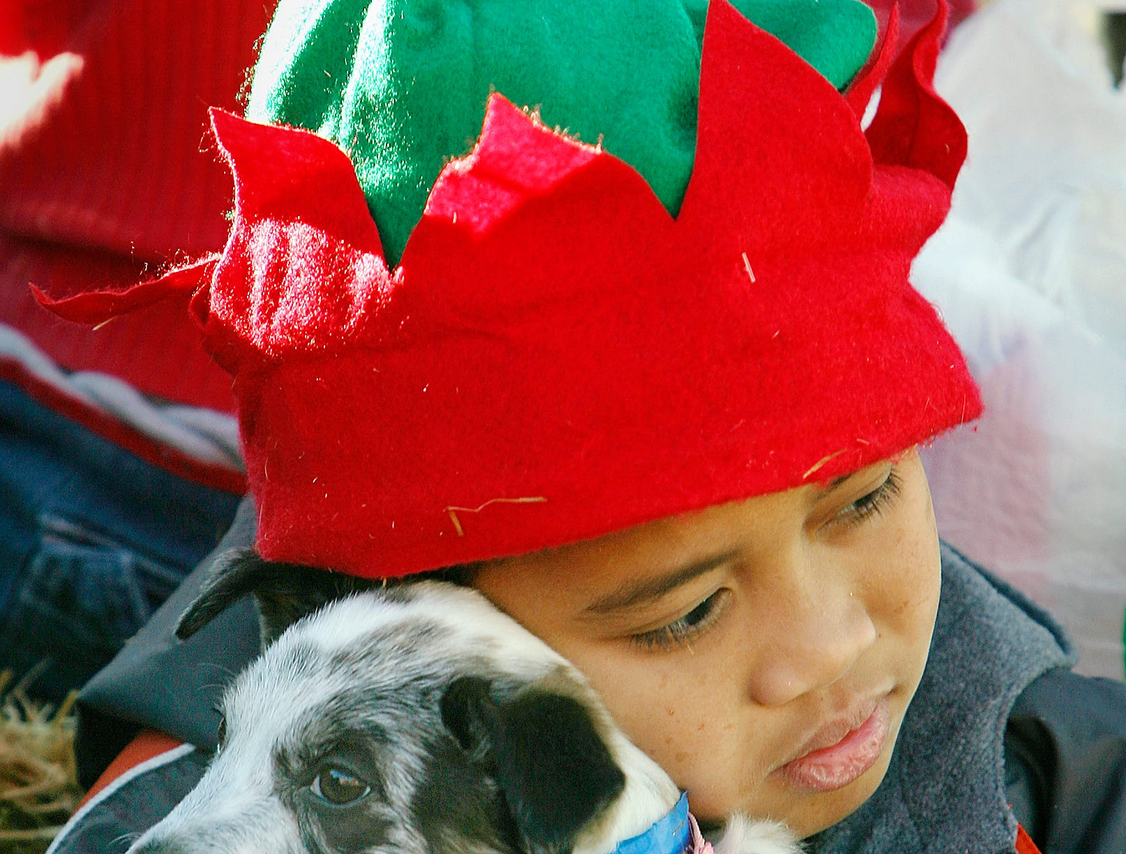 Marvin Prado of Iva hugs a puppy from the Anderson County Animal Shelter before the start of the city's Christmas parade in 2002. Workers from the shelter brought several dogs currently available for adoption to the parade.