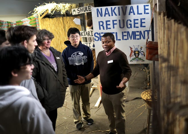 """Refugee specialist Joseph Kabamba leads visitors through a refugee camp Tuesday during the """"Coming Home"""" refugee experience simulation event put on by World Relief Fox Valley and Thrivent at the OuterEdge in Appleton."""