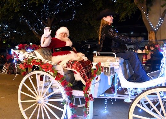 Santa Claus waves to the crowd during 2018's 30th anniversary City Sidewalks Christmas Lights Parade.
