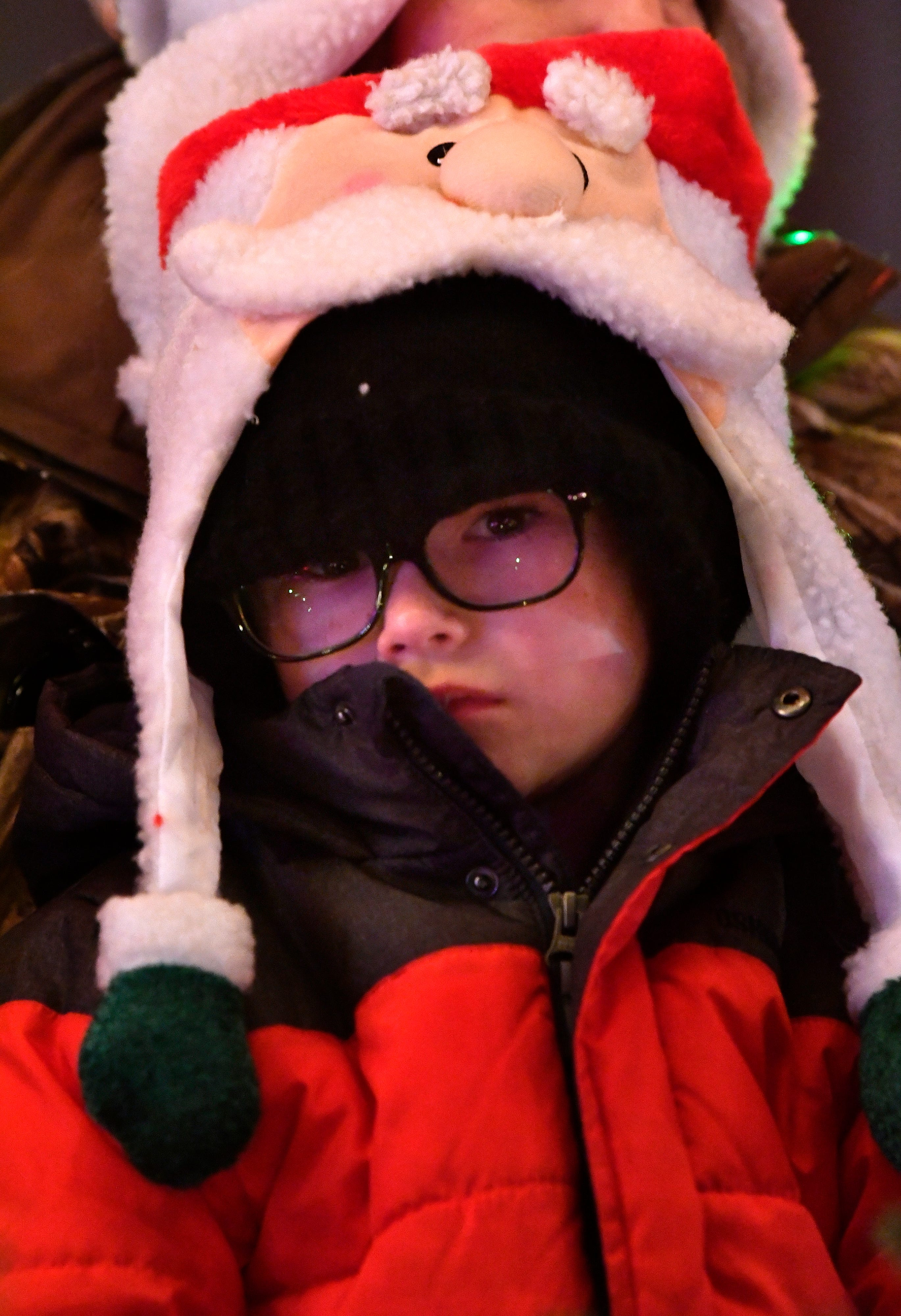 Carson Culp, 5, waits for the parade to start while sitting on the lap of his grandmother Jill Winters Tuesday. This was the 30th year for the City Sidewalks Christmas Lights Parade.