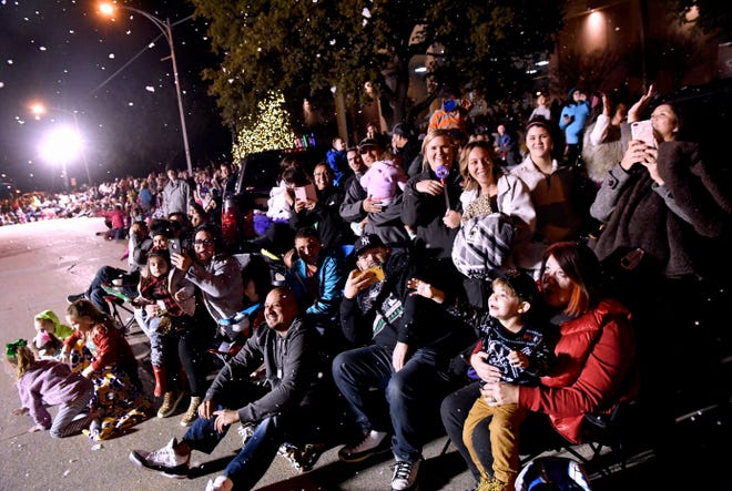 Spectators react as artificial snow is sprayed overhead from a float during Tuesday's parade. This was the 30th year for the City Sidewalks Christmas Lights Parade.