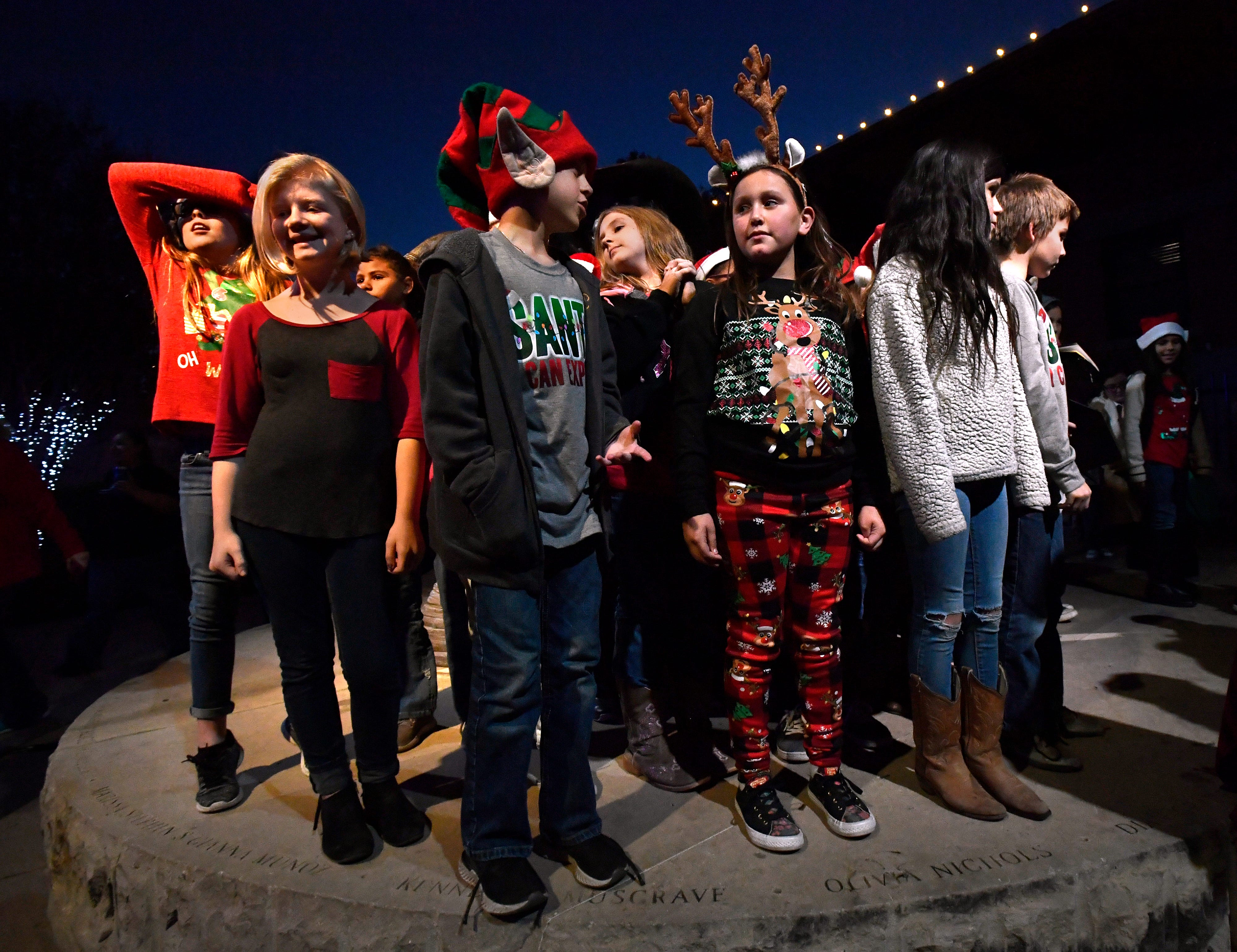 Fourth and fifth-graders from Bonham Elementary School wait to begin caroling at Everman Park Tuesday.