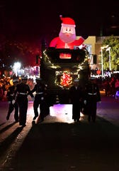 U.S. Marines and sailors are silhouetted as they walk ahead of their Toys for Tots truck during the 2018 City Sidewalks Christmas Lights Parade.