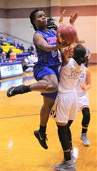 Cooper's Dazz Larkins, left, drives to the basket as Merkel's Alaunna White defends. Merkel beat the Lady Coogs 66-45 in the nondistrict game Tuesday, Nov. 27, 2018, in Merkel.