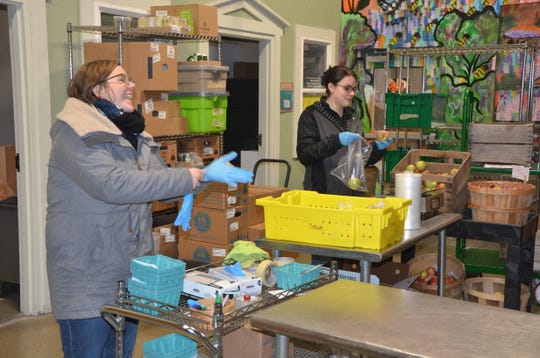 Hub Manager Brennan Dougherty (left) and Food Hub Team Member Sunny Richards pack Sprout Boxes at Sprout's 503 Military St. location in Springfield on  Tuesday, Nov. 27, 2018.