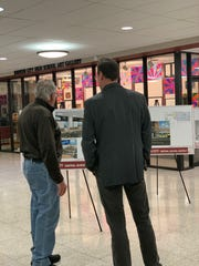 Two men look at potential plans.