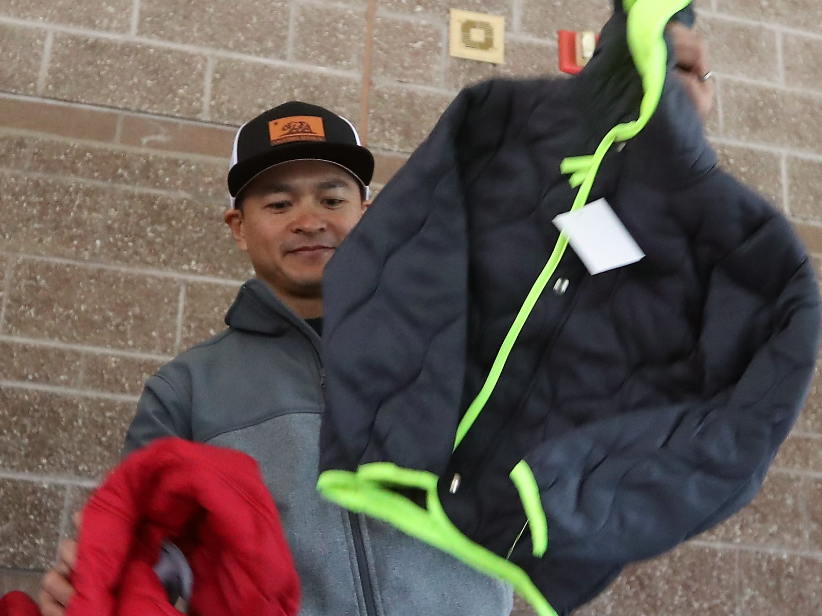 Bremerton firefighter Carlo Celeste pulls new coats out boxes as he and fellow firefighters and volunteers help with Coats for Kids event held at Kitsap Lake Elementary School on Wednesday, November 28, 2018.