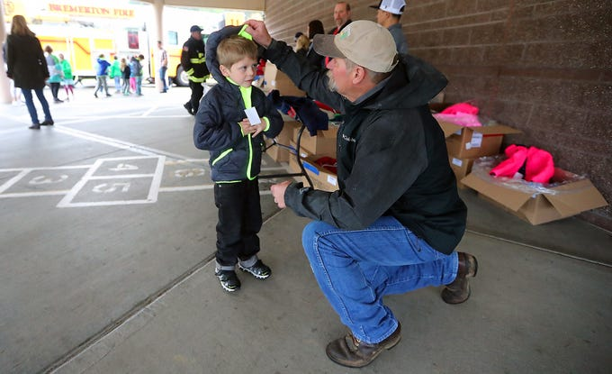 Bremerton Fire Department's Lt. Raymond Grahn helps Kenny Templeton, 8, put up the hood on the new jacket he received as part of the Kitsap Fire Fighters Benevolent Fund annual Coats for Kids event held at Kitsap Lake Elementary School on Wednesday, November 28, 2018. Firefighters from around Kitsap distributed 225 American made coats to classrooms at Wolfe Elementary School and Kitsap Lake Elementary.
