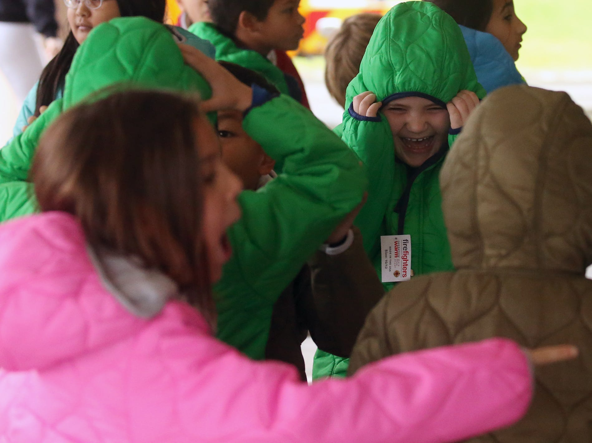 Students laugh and try out the hoods on their new coats during the annual Coats for Kids event held at Kitsap Lake Elementary School on Wednesday, November 28, 2018.