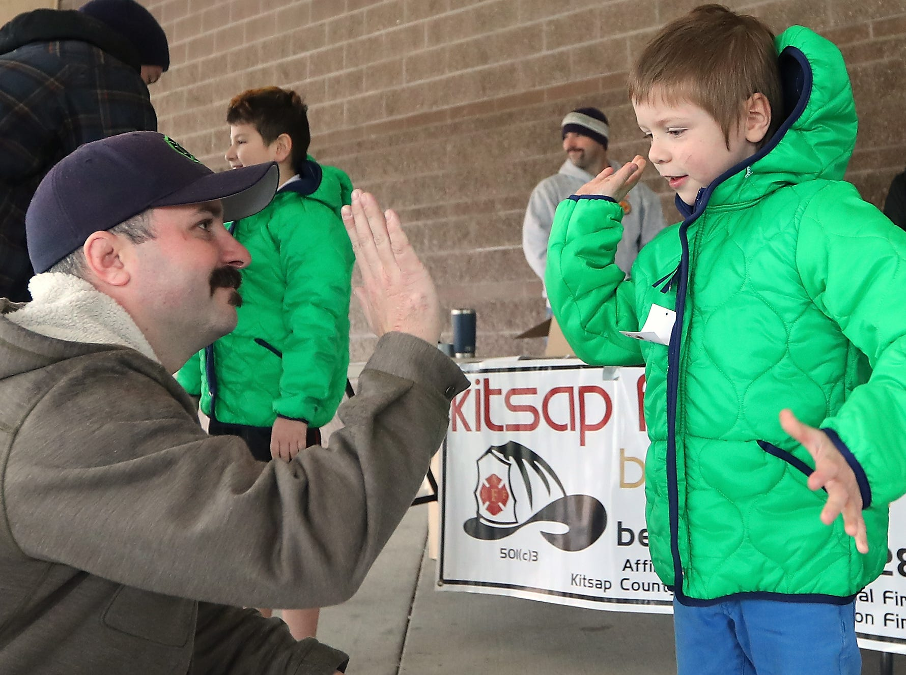 Bremerton firefighter Rickey Muttart gets a high-five from student Damen Bisbee, 8, after Bisbee and fellow classmates received new coats as part of the Kitsap Fire Fighters Benevolent Fund annual Coats for Kids event held at Kitsap Lake Elementary School on Wednesday, November 28, 2018.