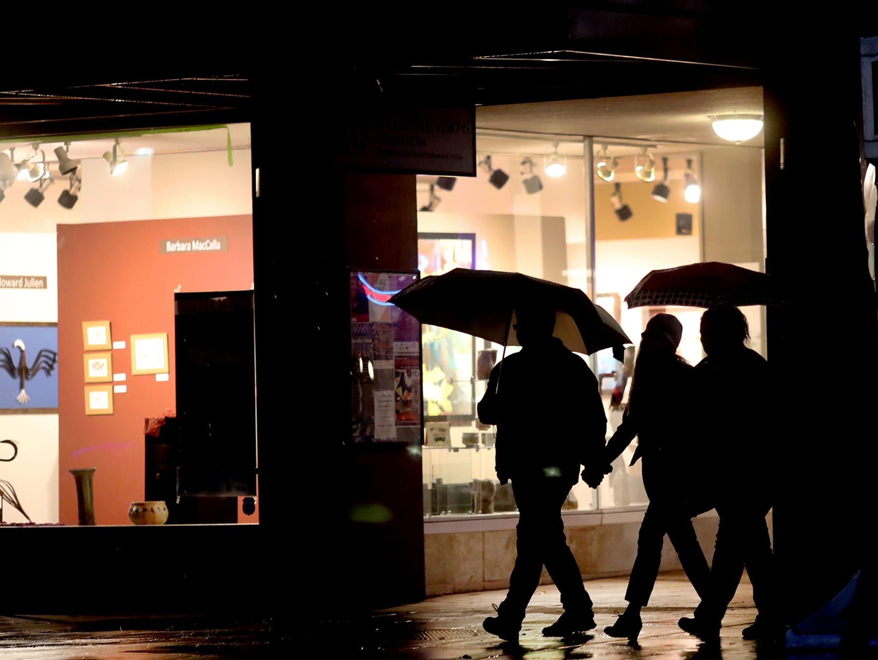 Umbrellas are needed on a sloppy wet walk on Fourth and Pacific in downtown Bremerton at the Collective Visions gallery on Tuesday, November 27, 2018.