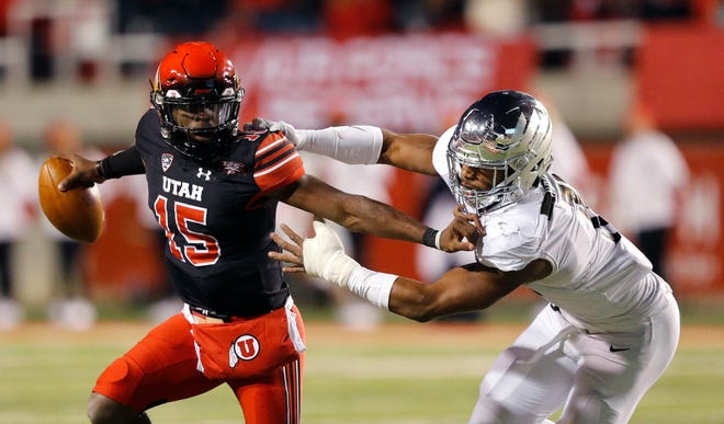 Utah quarterback Jason Shelley stiff-arms Oregon linebacker Justin Hollins during a game this year in Salt Lake City.  The Washington Huskies will face Shelley's Utes in the Pac-12 Championship game on Friday.